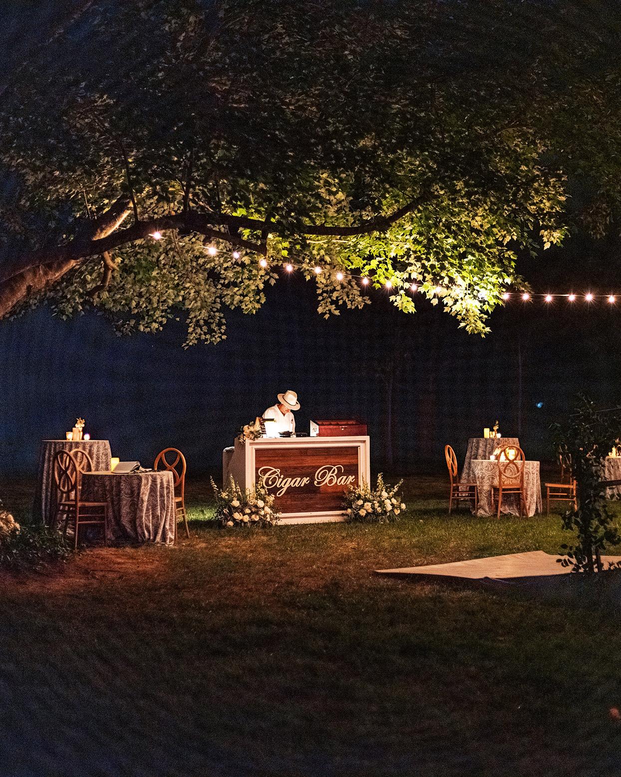 lauren chris wedding cigar bar lit under trees