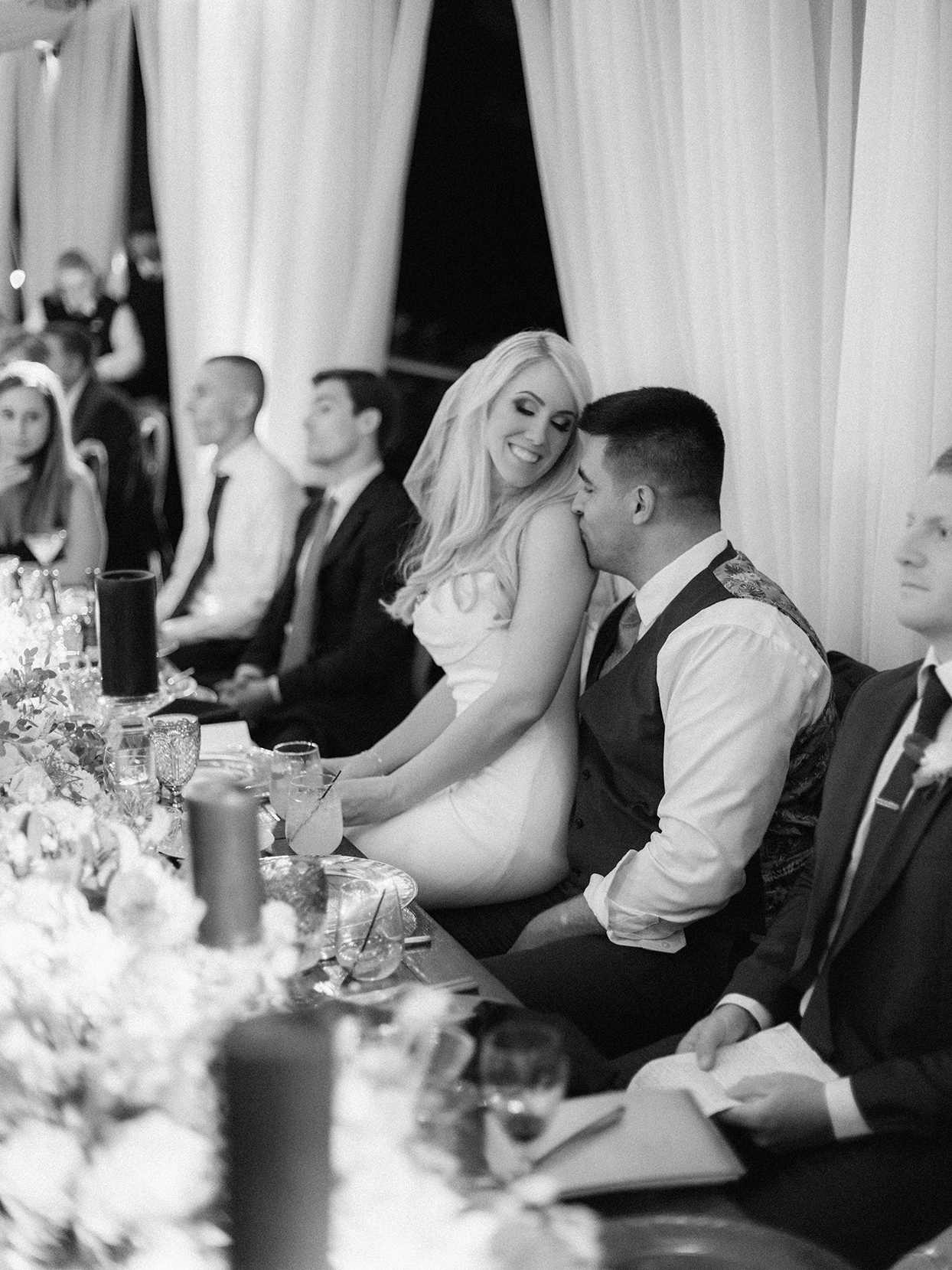 lauren chris wedding bride sitting on groom's lap at reception