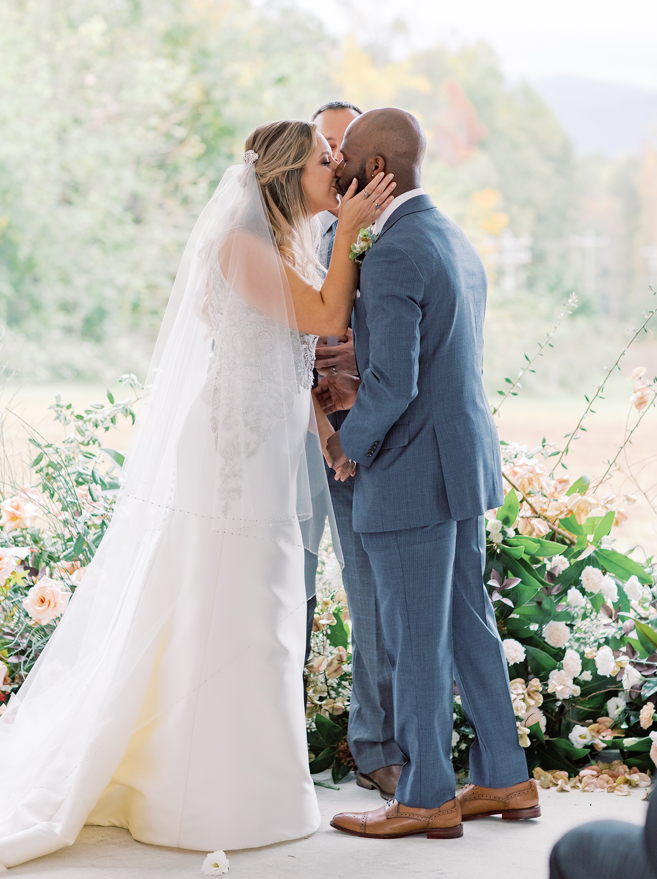 outdoor wedding ceremony couple kiss floral sculpture