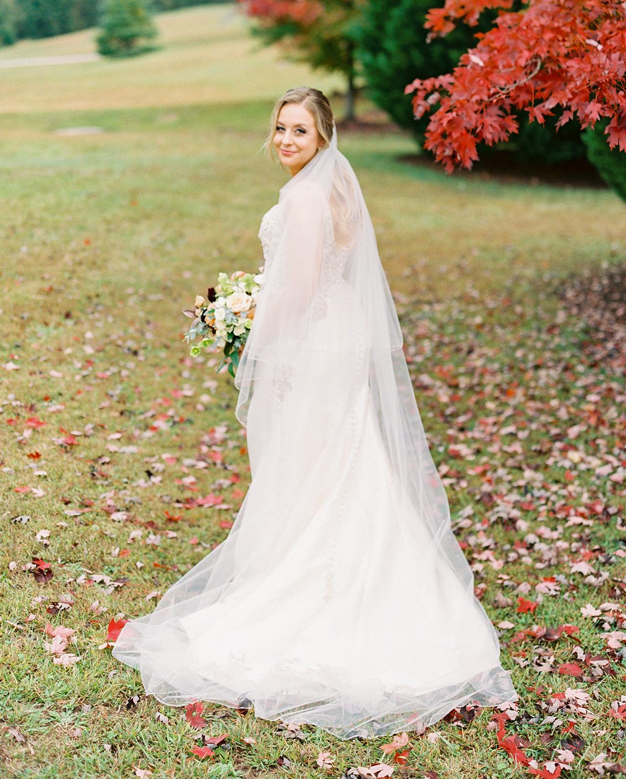 bride posing near red leaf tree in wedding dress