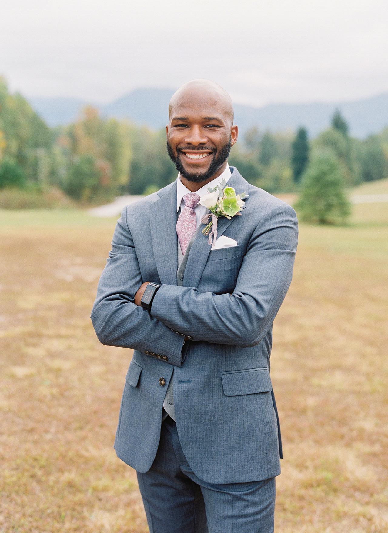 groom posing outdoor blue tuxedo mountain landscape