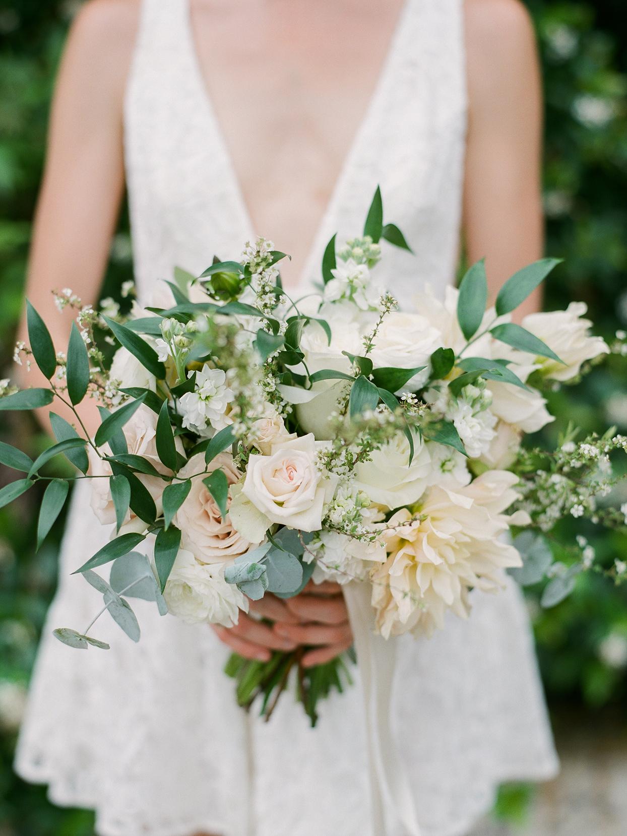 Bride with bouquet of white O'Hara garden roses, cafe au lait dahlias, ranunculus, mixed eucalyptus, and jasmine