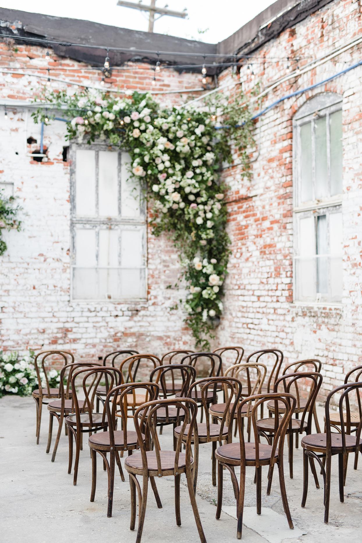 Wedding chair setup with flowers in brick corner