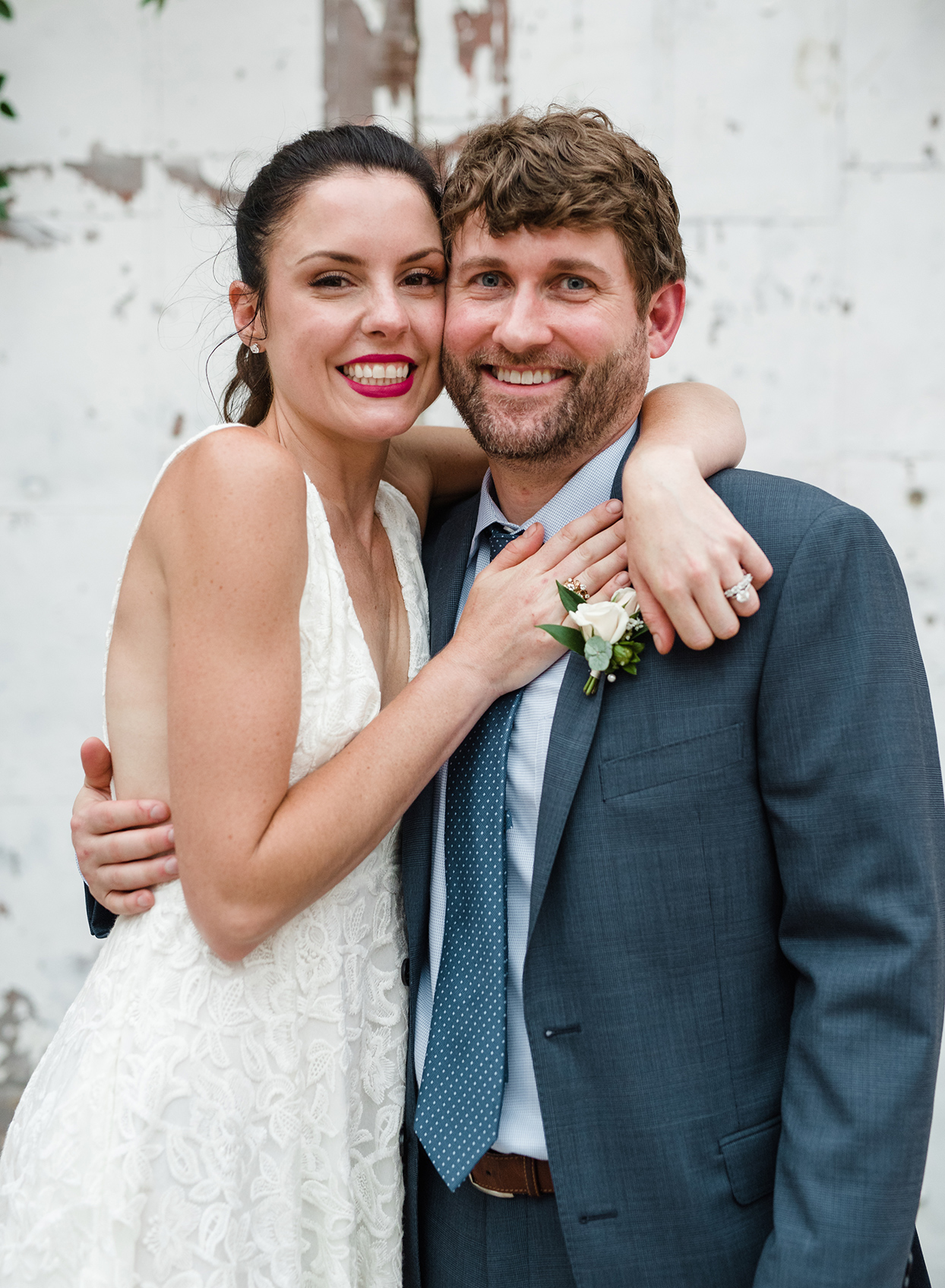 Wedding couple hugging in front of warehouse