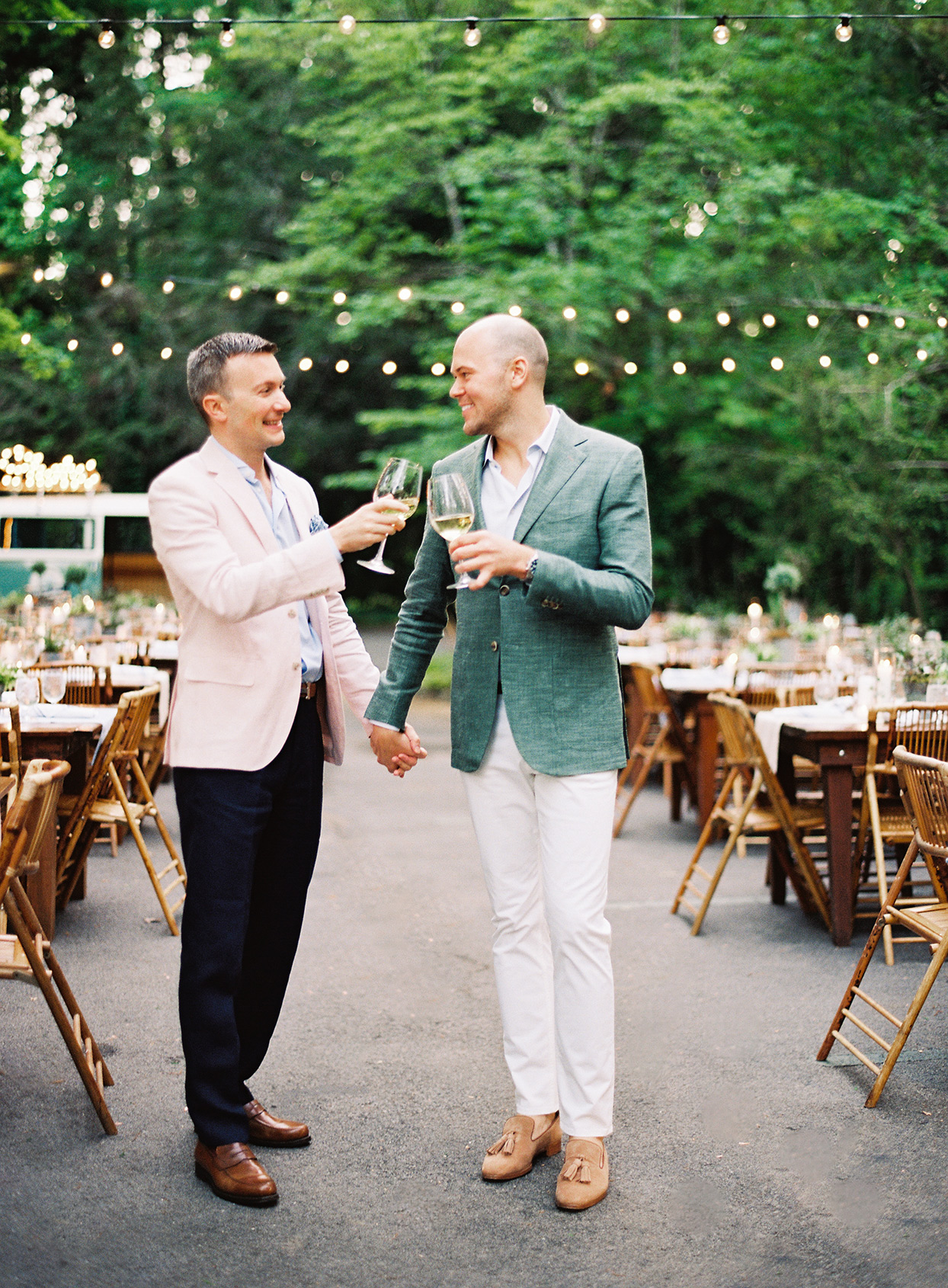 grooms toasting each other standing by tables at welcome party