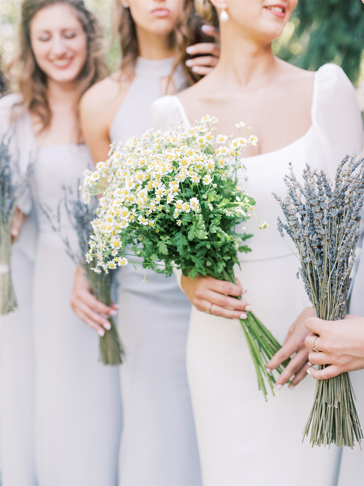 bridesmaids in pastel blue holding wildflowers