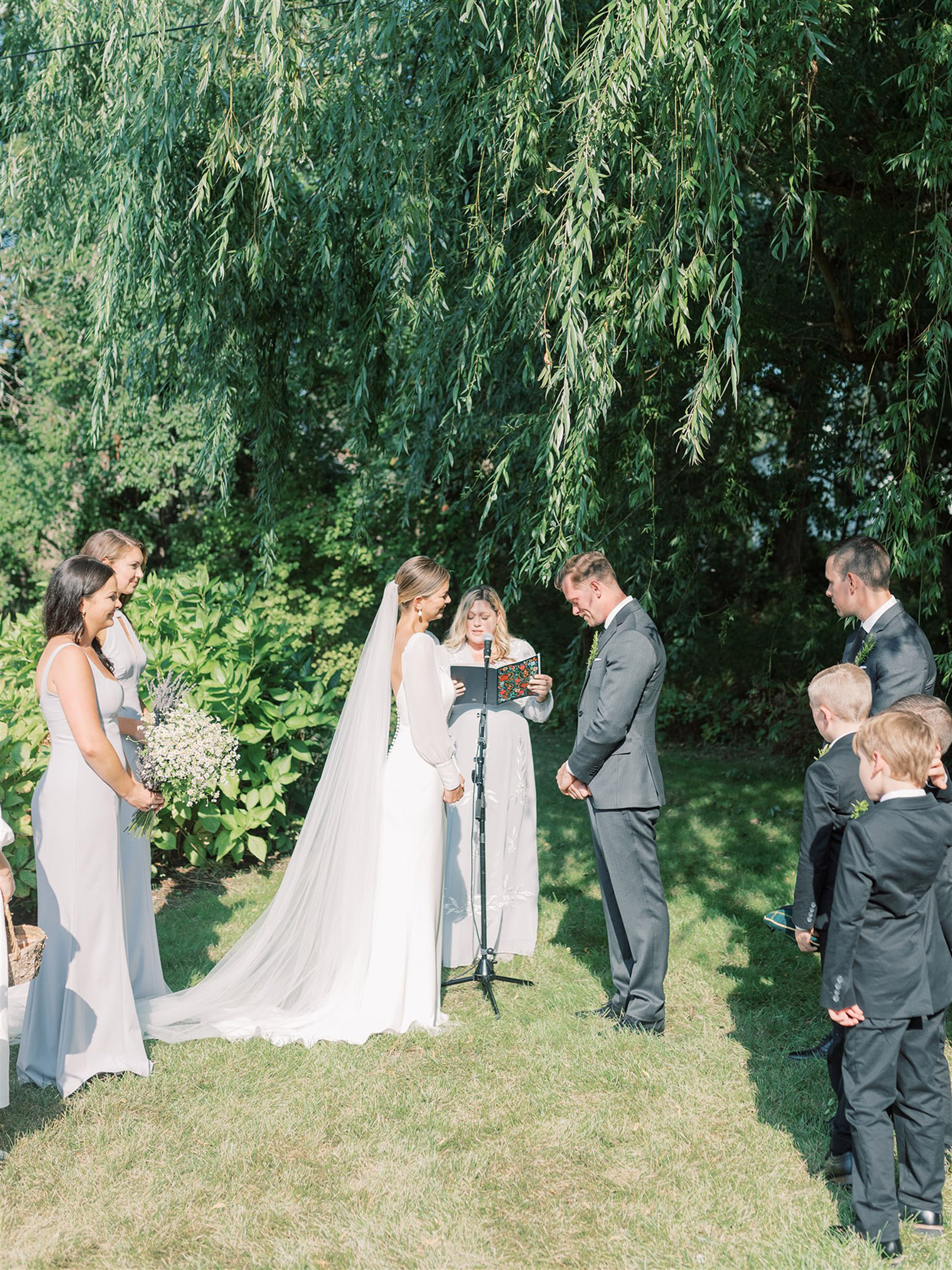 samantha cody wedding ceremony in grass with tree backdrop