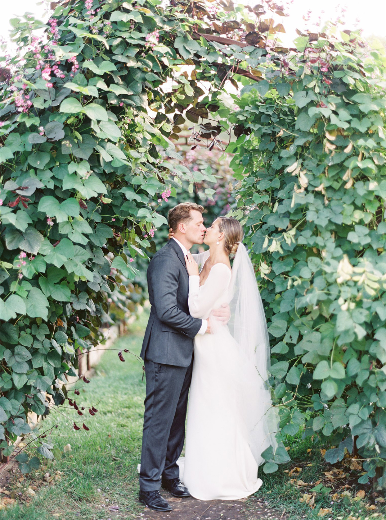 samantha cody wedding couple kissing under archway of greenery