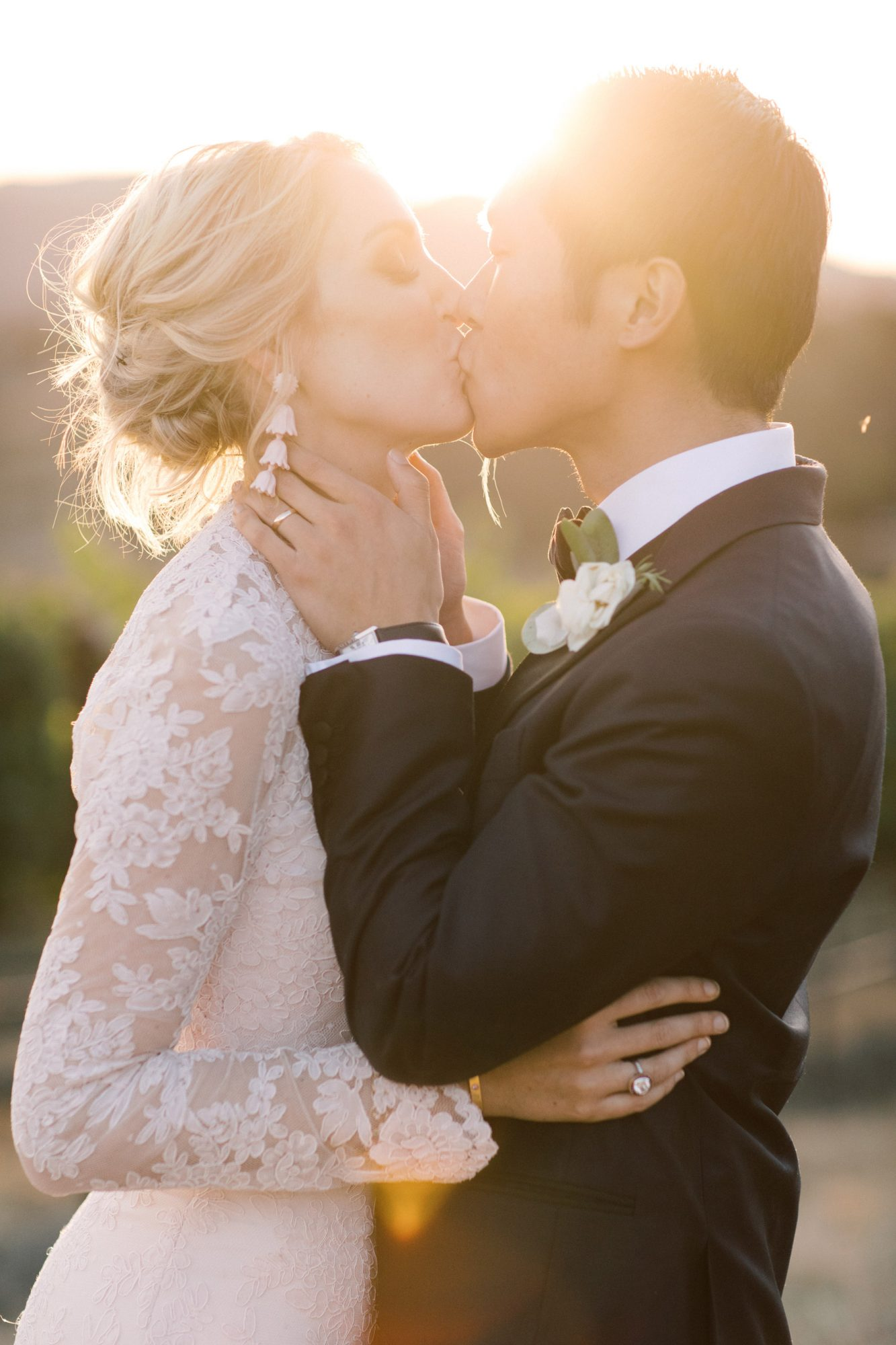 wedding couple kissing with sun shining in background