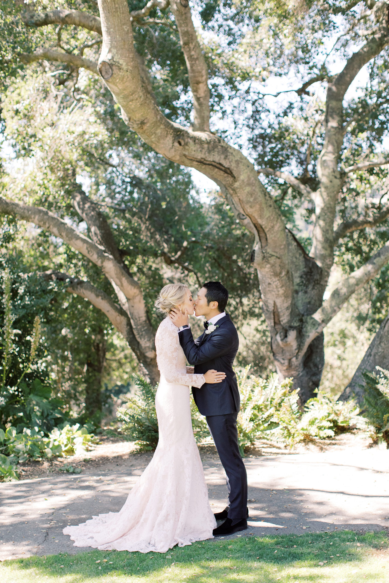 Sarah and Tengbo kissing under tree first look