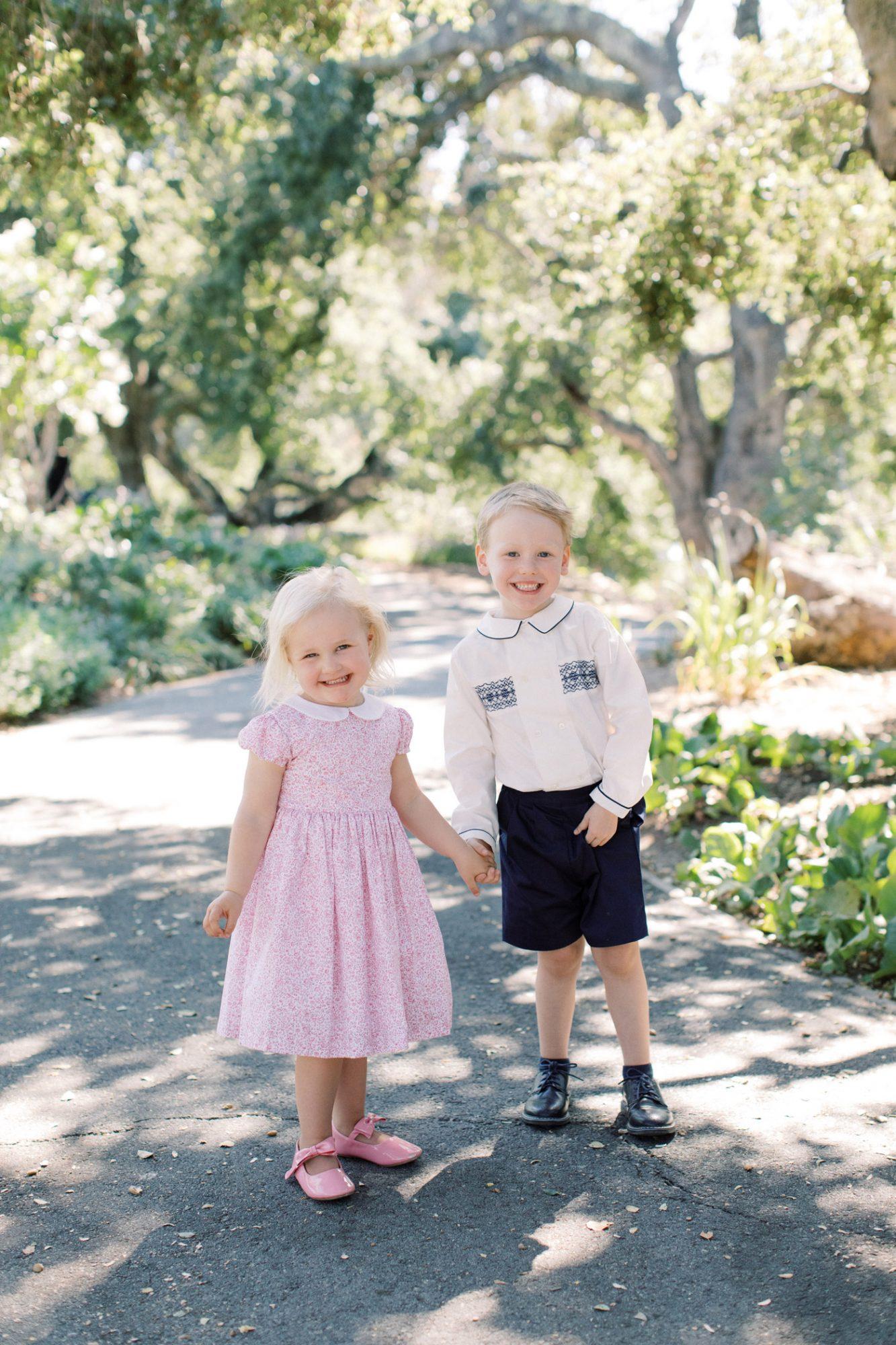 flower girl and ring bearer portrait holding hands outside