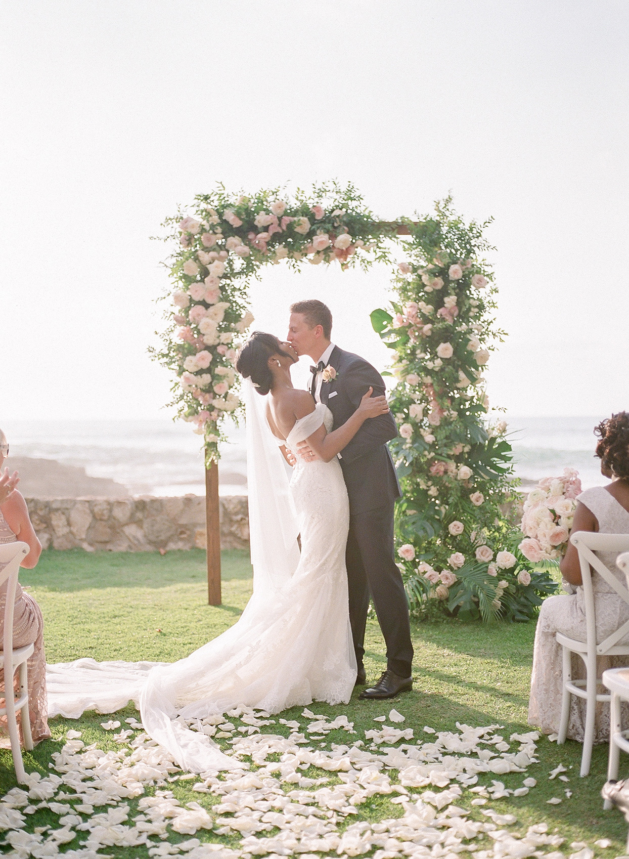 vanessa nathan wedding ceremony kiss in front of floral arch
