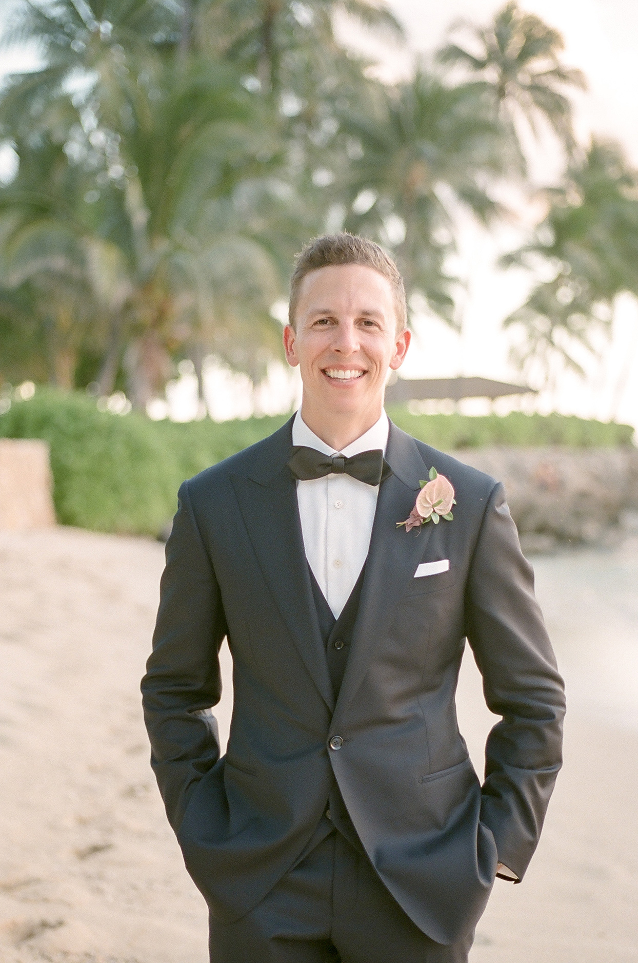 vanessa nathan wedding groom in gray suit on beach