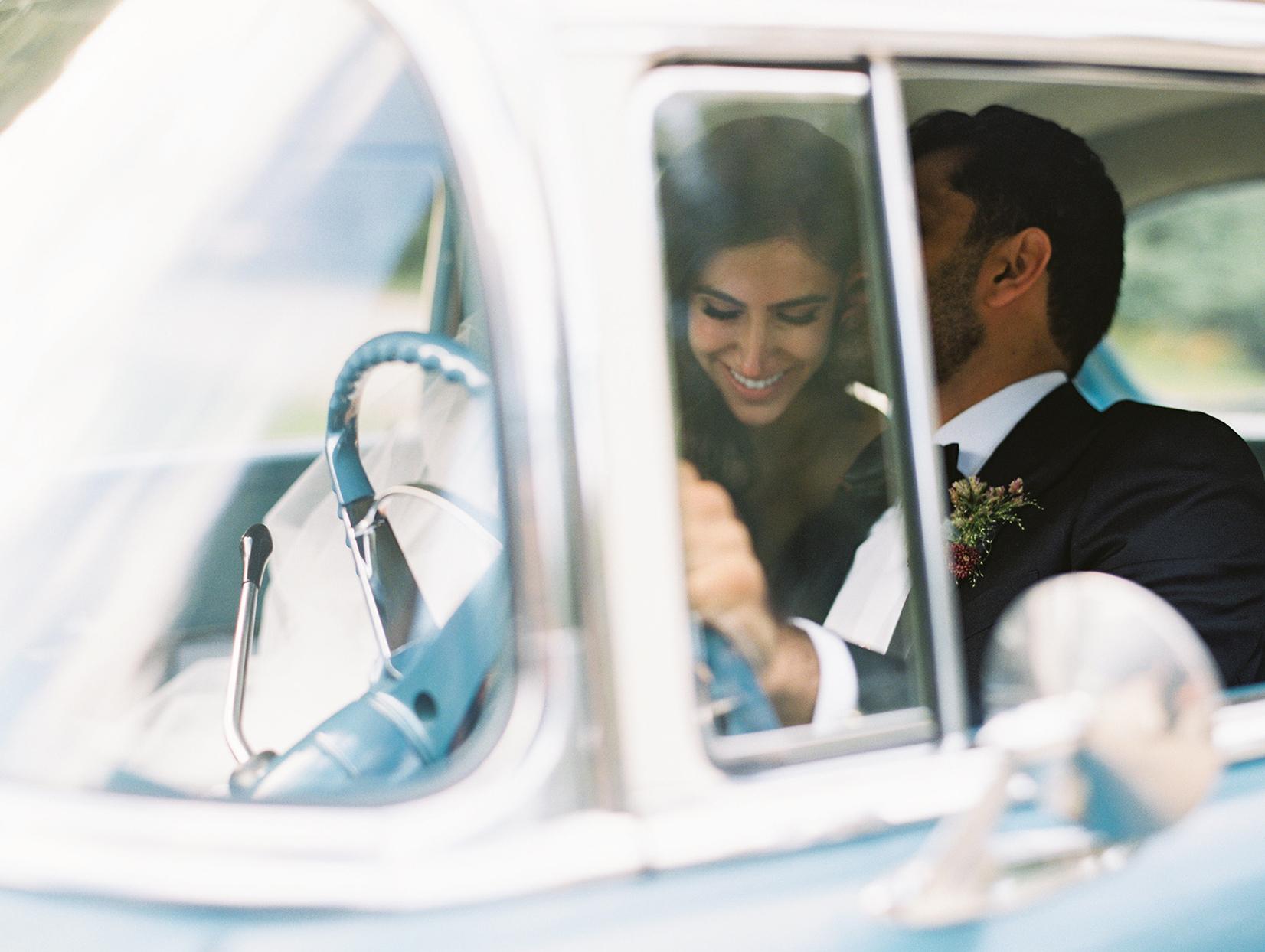 yalda anusha wedding couple with heads together in blue vintage car