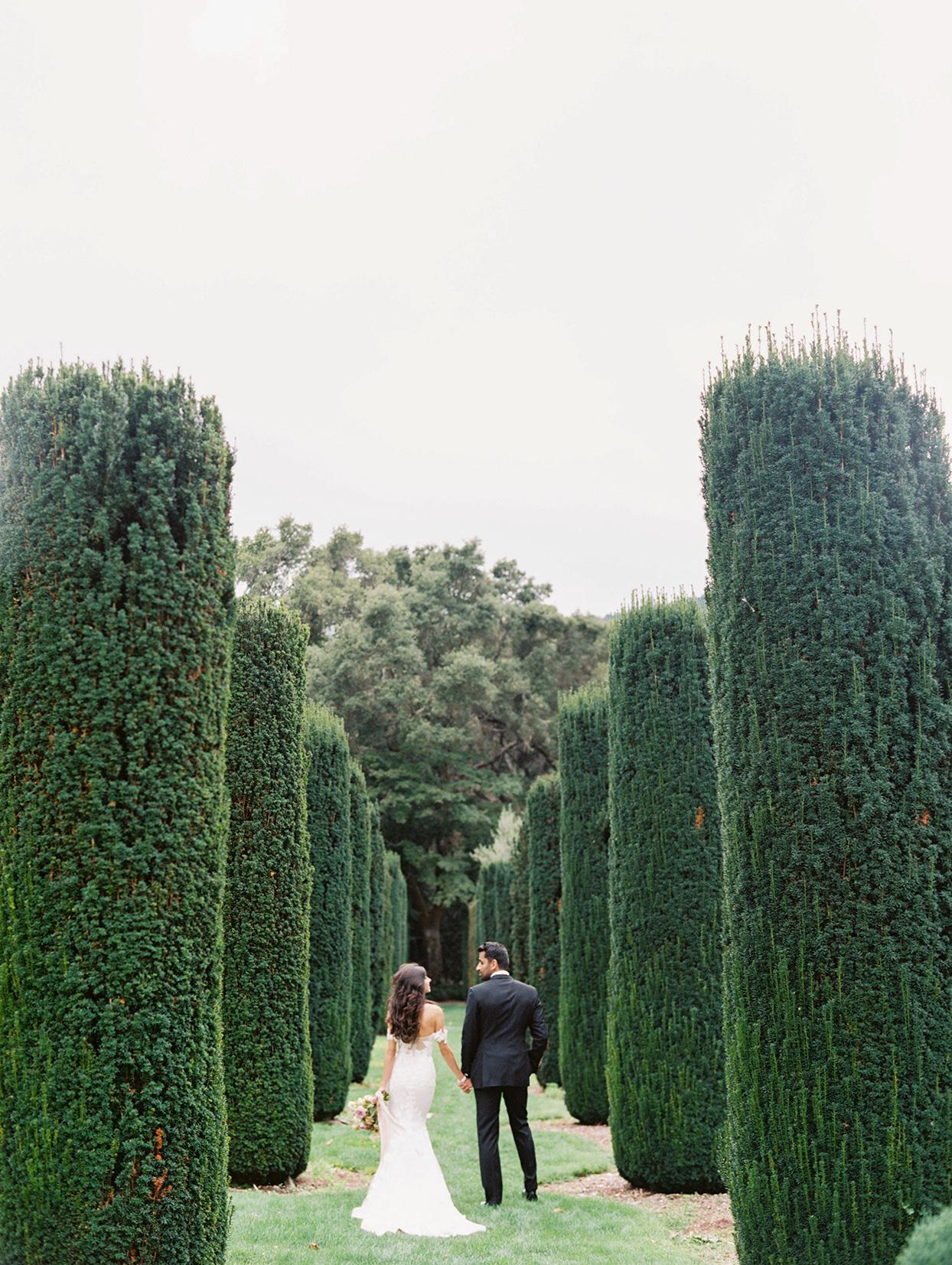 yalda anusha wedding couple walking through tall garden trees