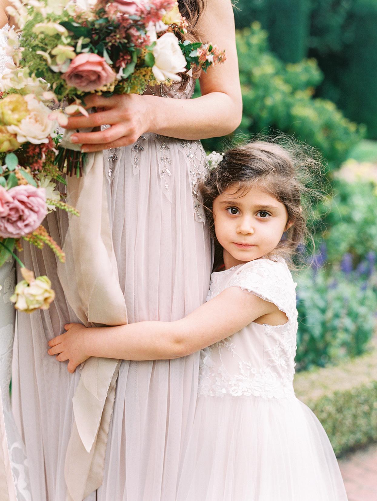 yalda anusha wedding flower girl hugging bridesmaid in pastel pink dress