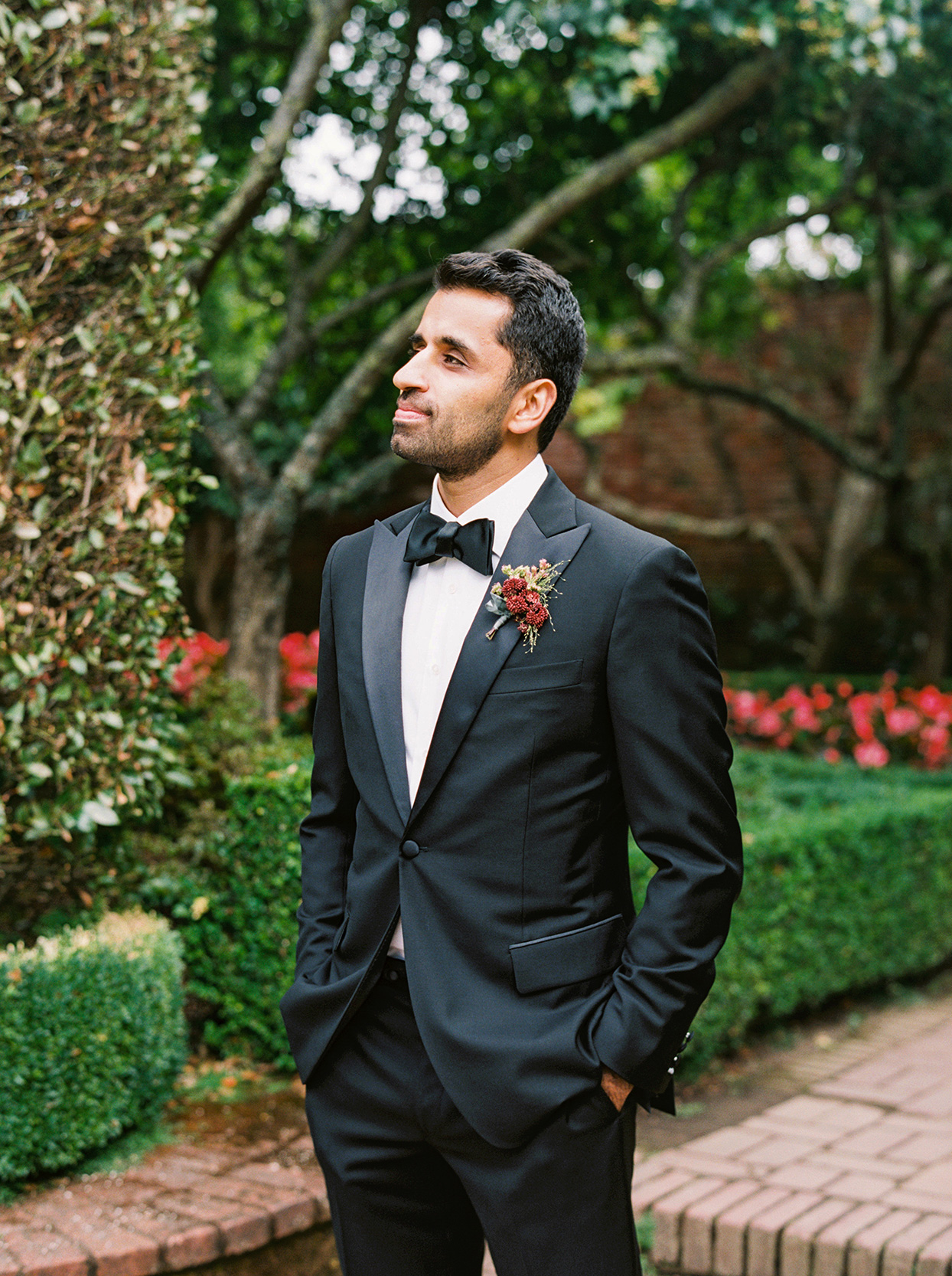 yalda anusha wedding groom in black tux with red floral boutonniere