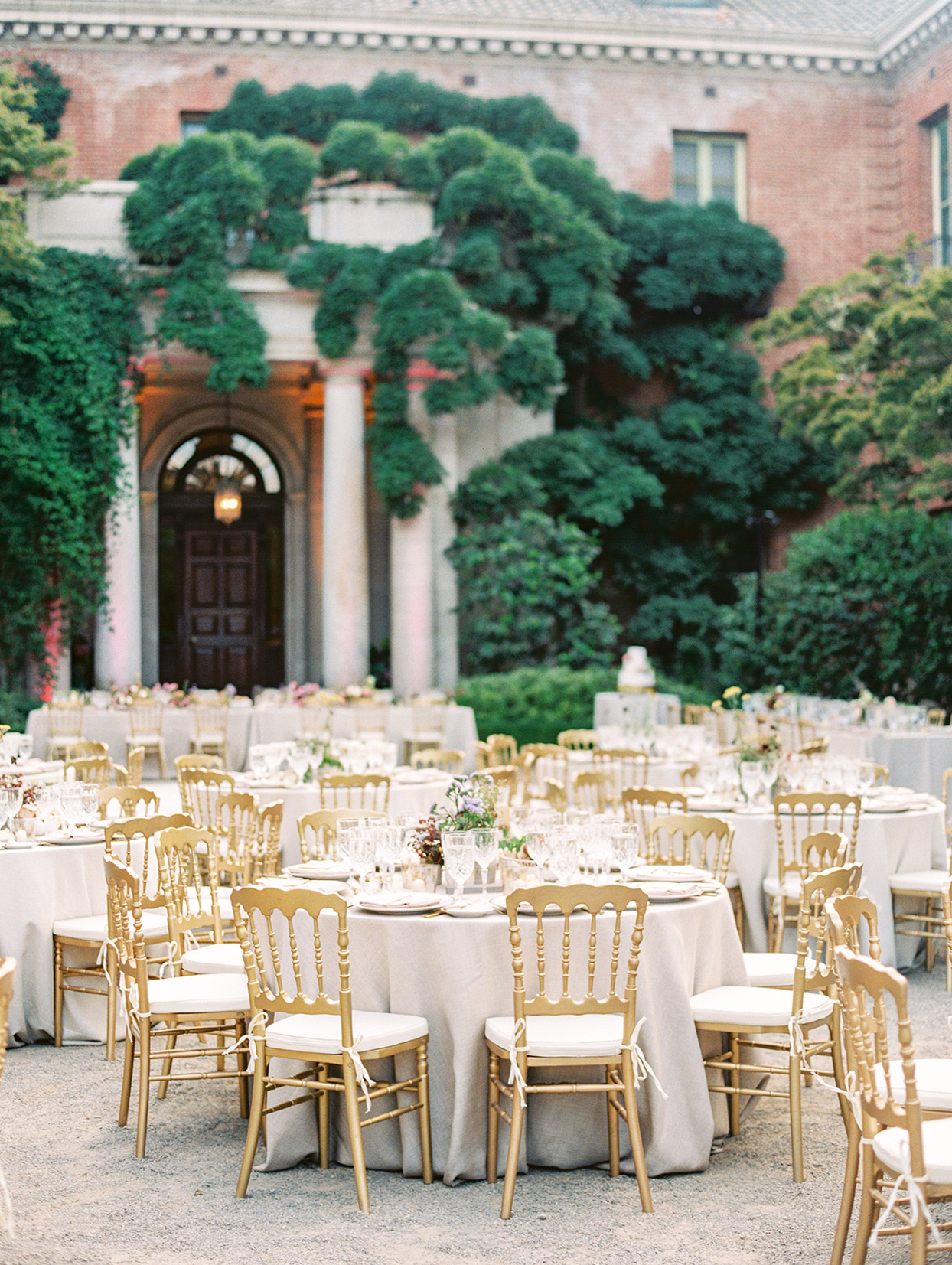yalda anusha wedding reception round tables outdoors with gold chairs