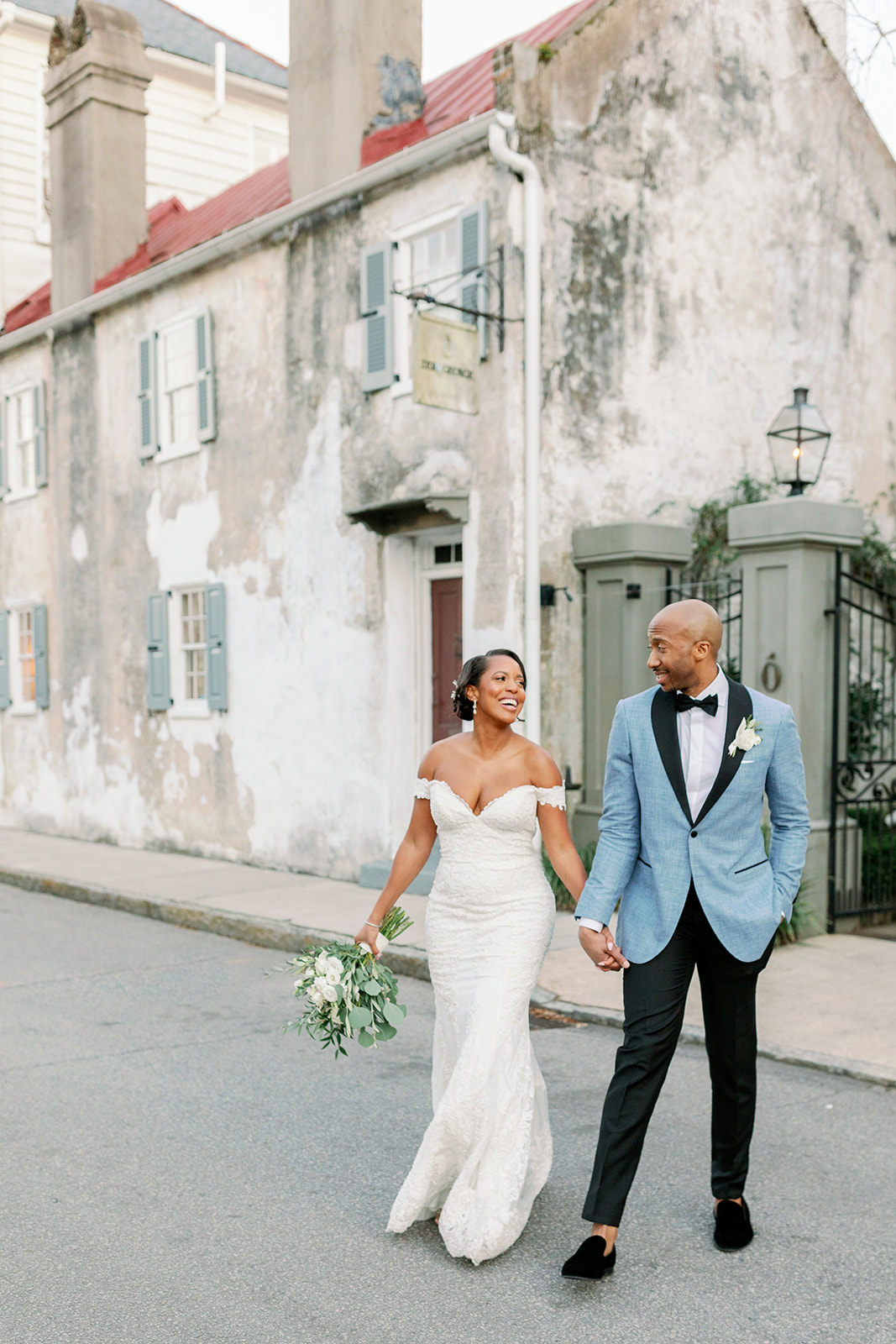 Couple walking together in road in front of rustic building