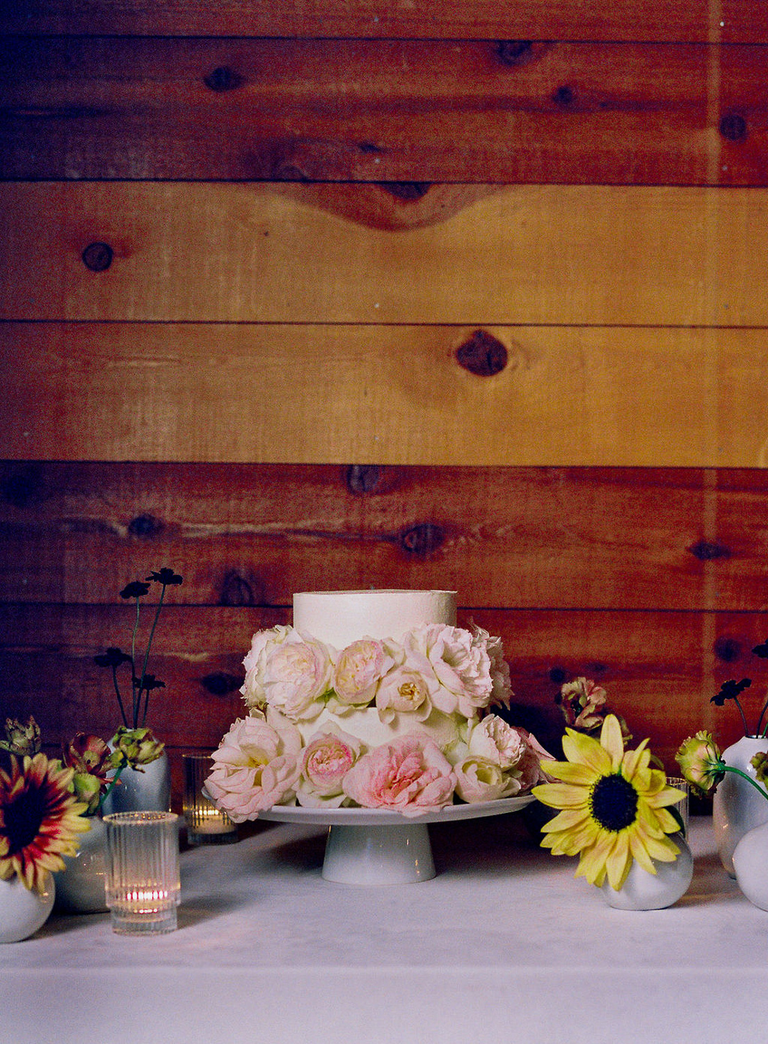 small wedding cake with pink peonies against wood wall
