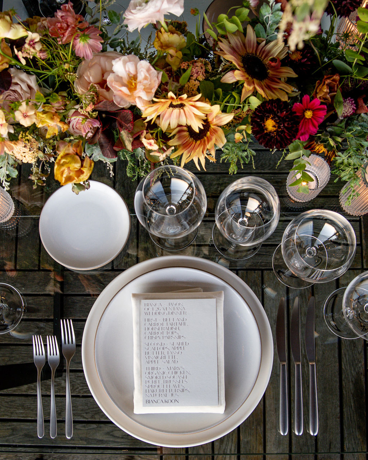 wedding place setting with white plates and warm tones flowers