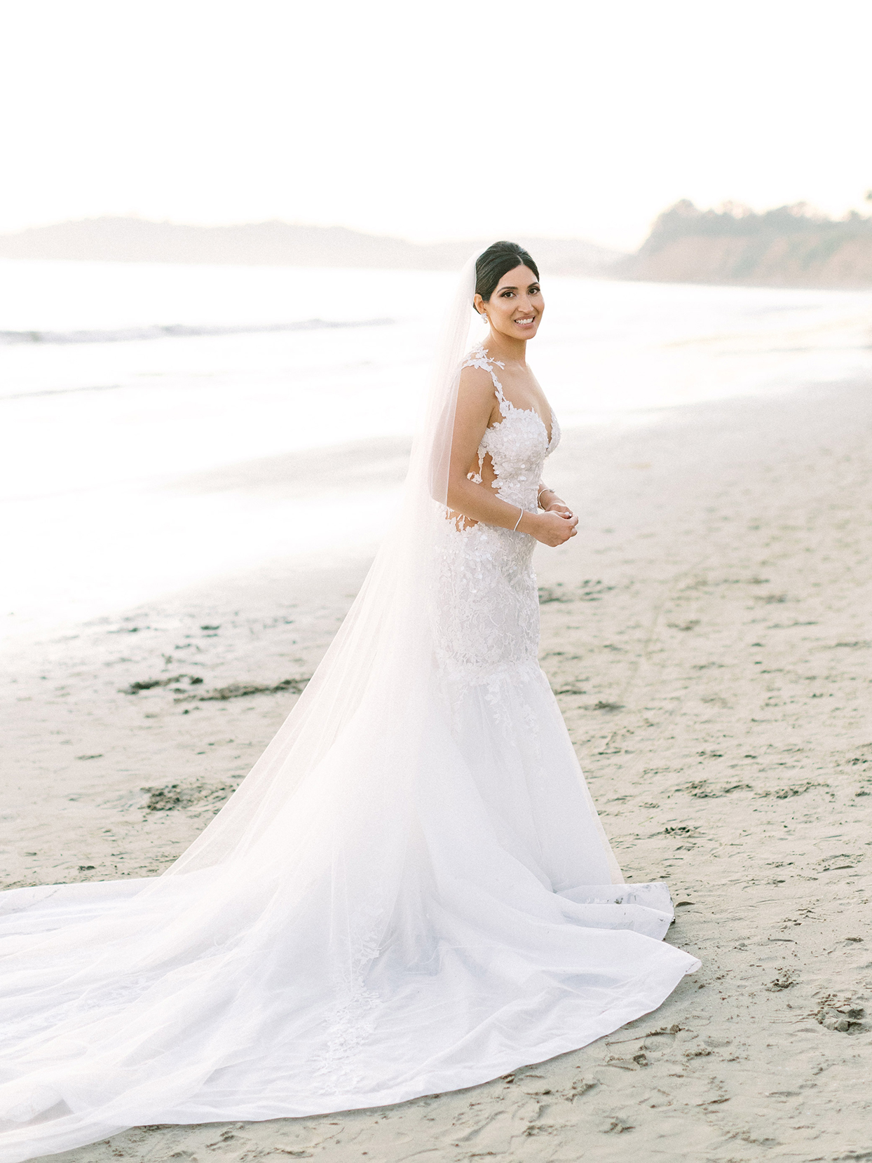 bride in white gown standing on beach