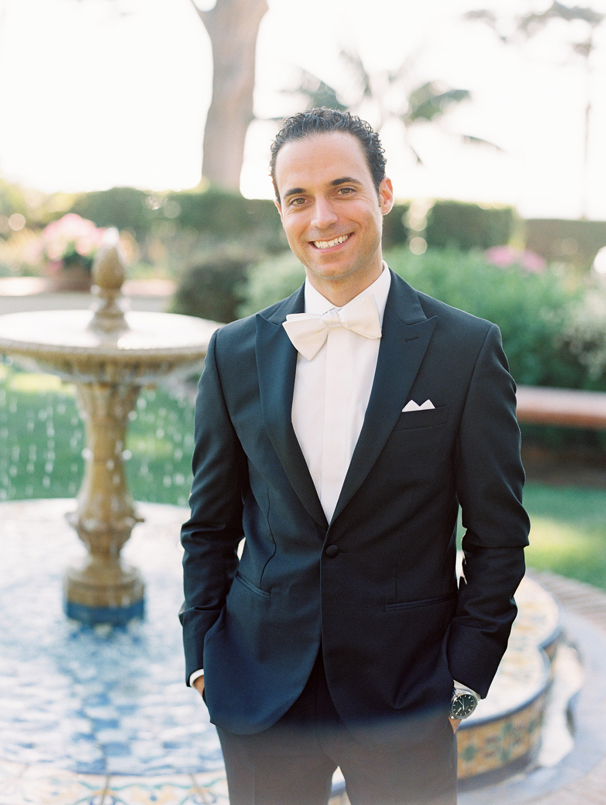 groom in black suit with white bowtie