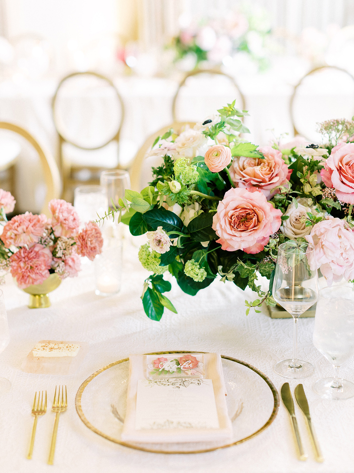 elegant reception place setting with golden accents and pink floral arrangement