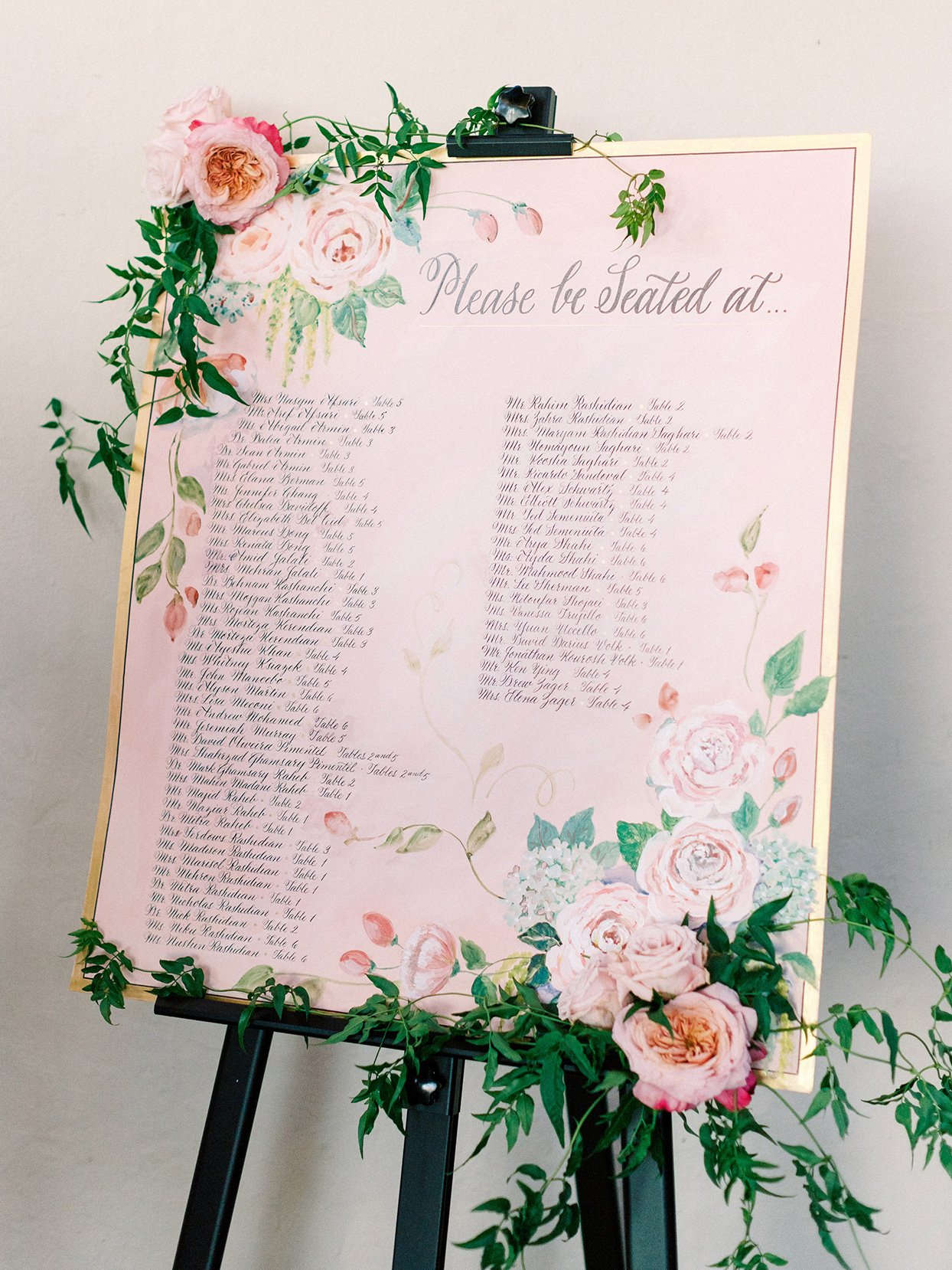 large pink and gold seating chart board with floral accents