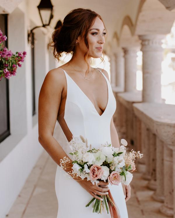 bride holding pastel bouquet on elegant balcony