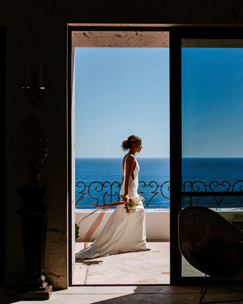 through tall doorway view of bride walking along balcony over ocean