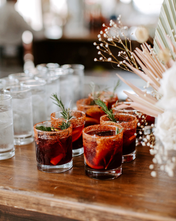 wedding cocktails on wooden table next to water glasses