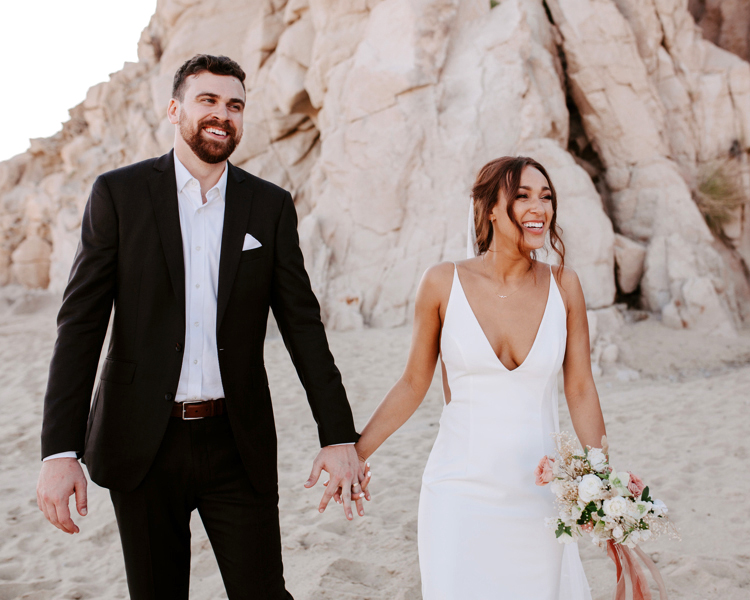 wedding couple holding hands and walking on the beach