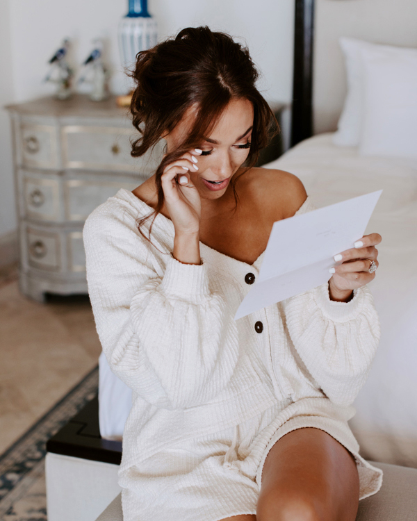 bride reading a letter while getting ready