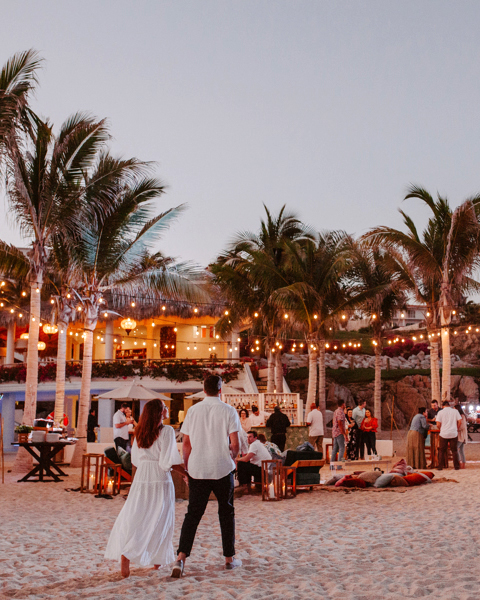 couple walking at beach welcome party at night