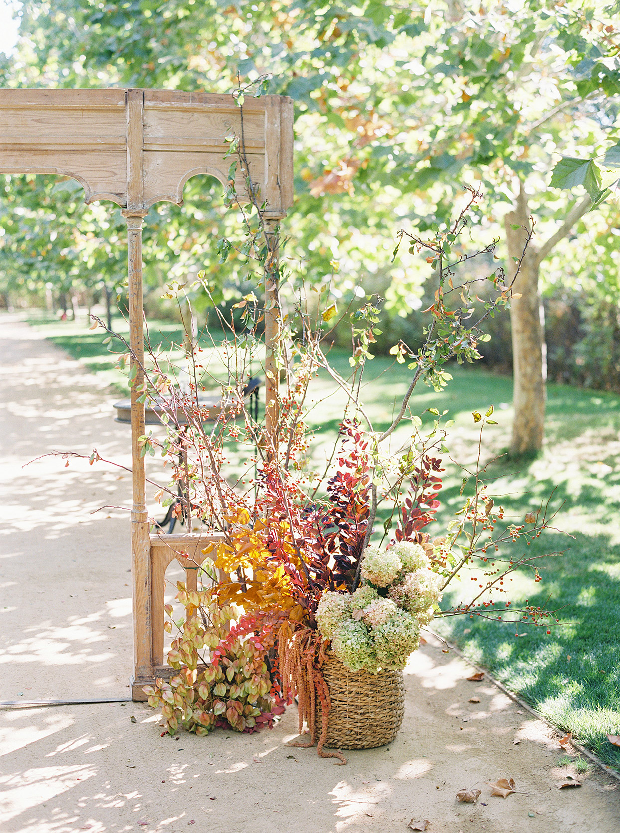 dried and rustic fall flowers against wooden ceremony backdrop