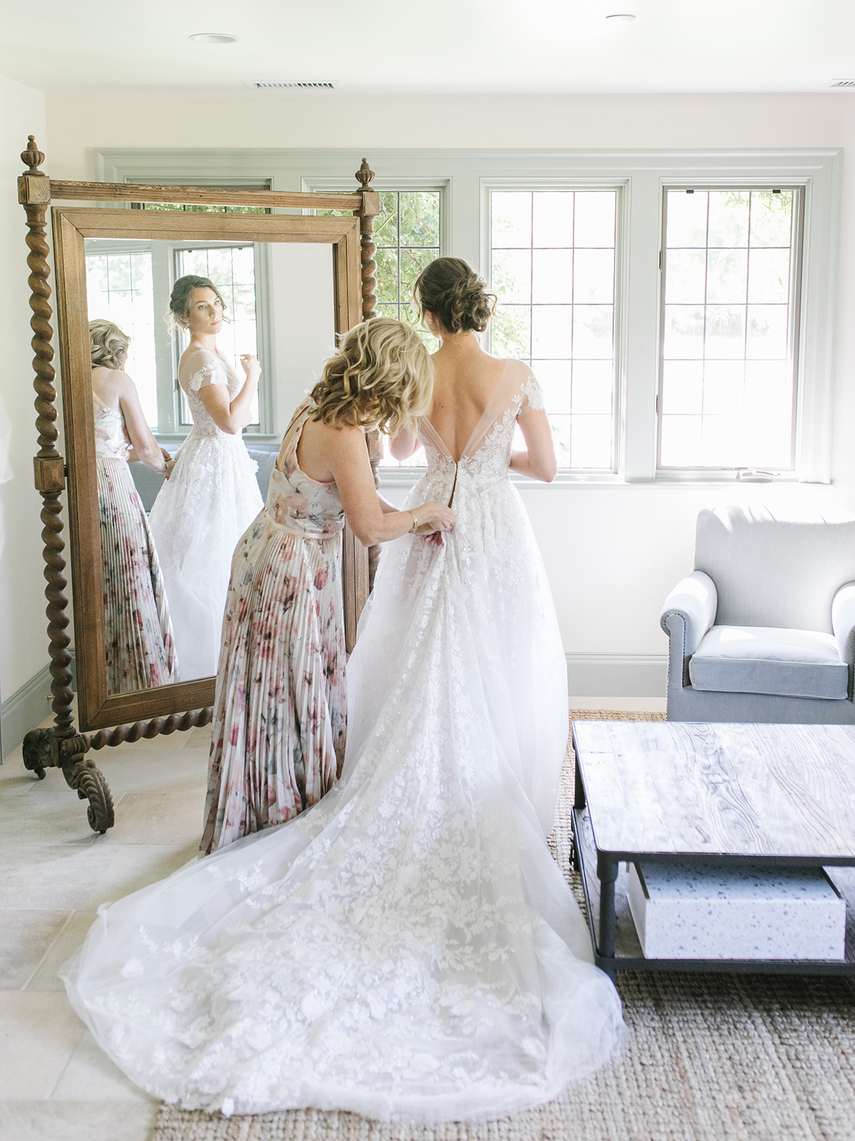 bride helping bride get ready in front of mirror