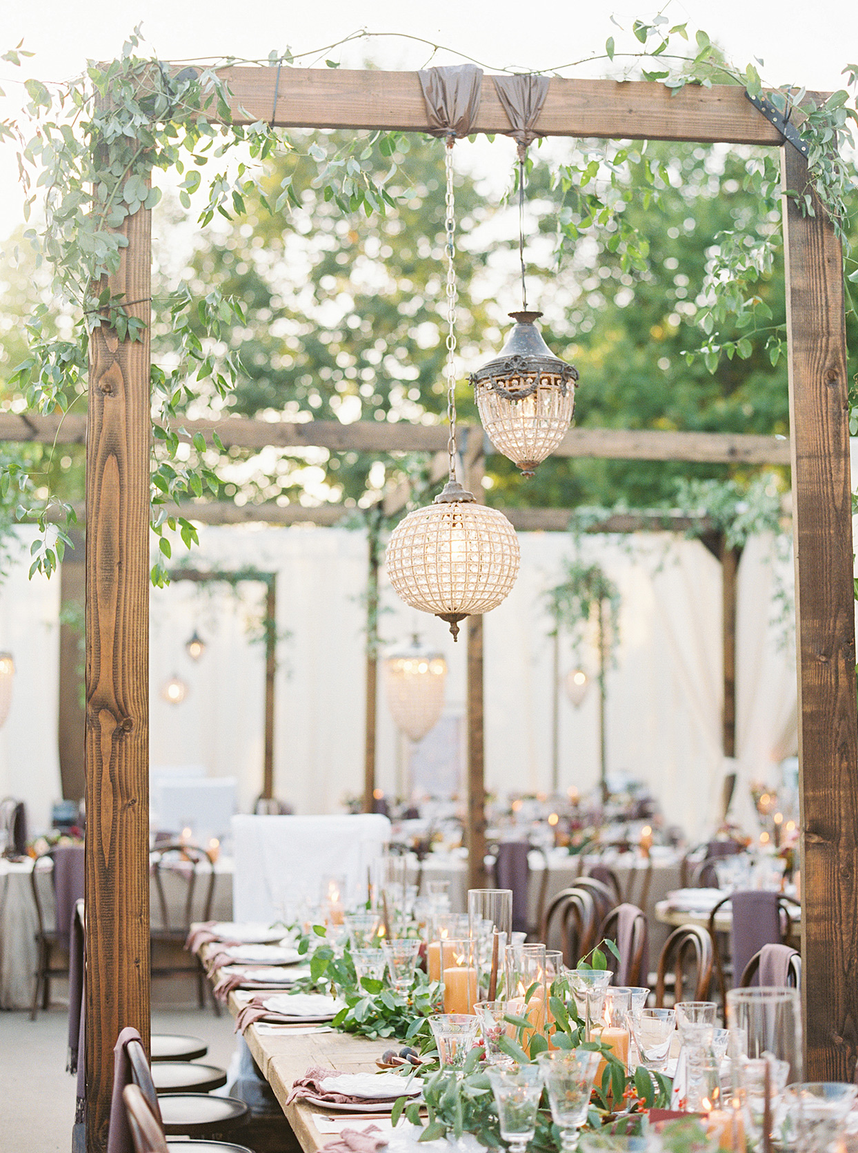 sam kyler wedding reception table with wooden installment and hanging lanterns