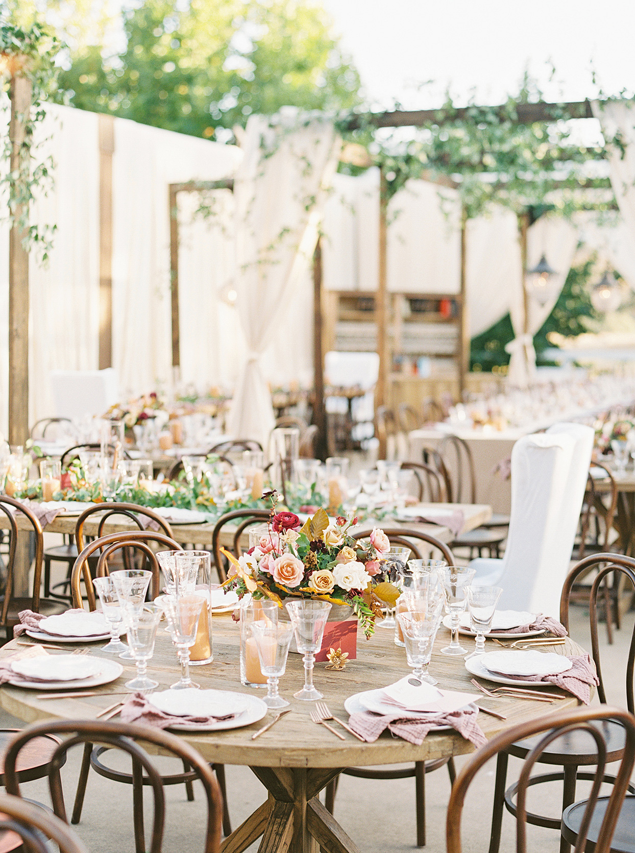 round wooden reception tables with rustic fall flower bouquets