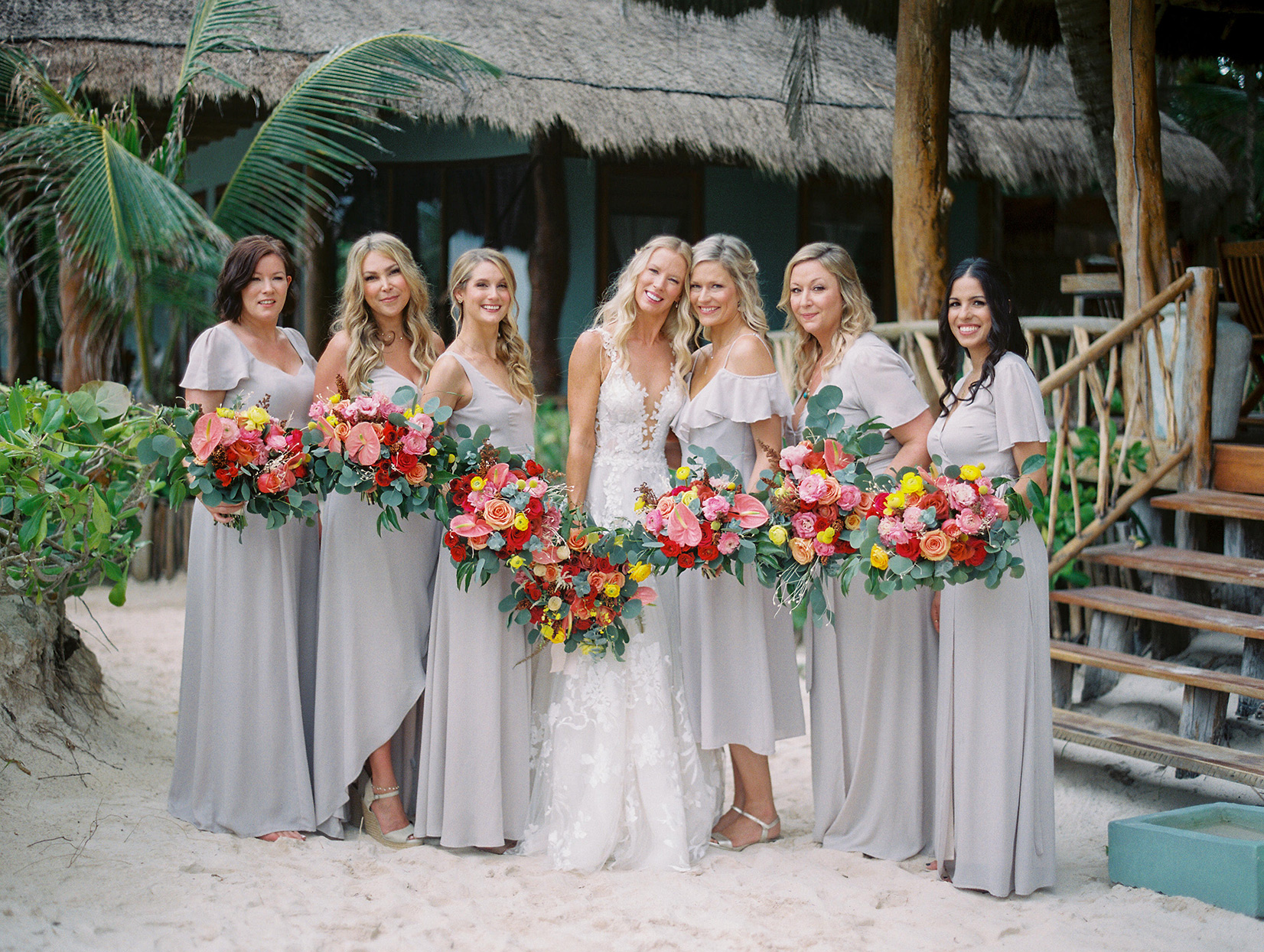 bride and bridesmaids in light gray holding red and yellow bouquets