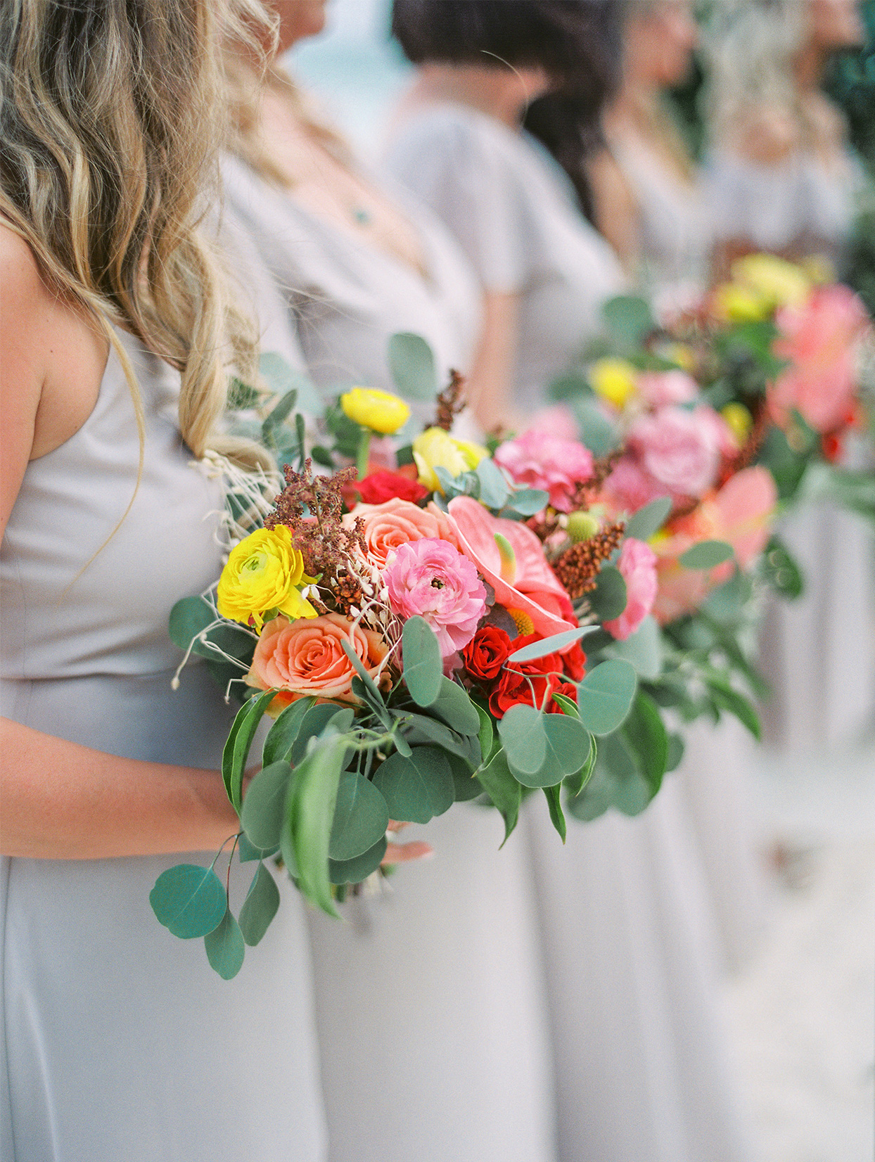 bridesmaids in light gray holding colorful wedding bouquets