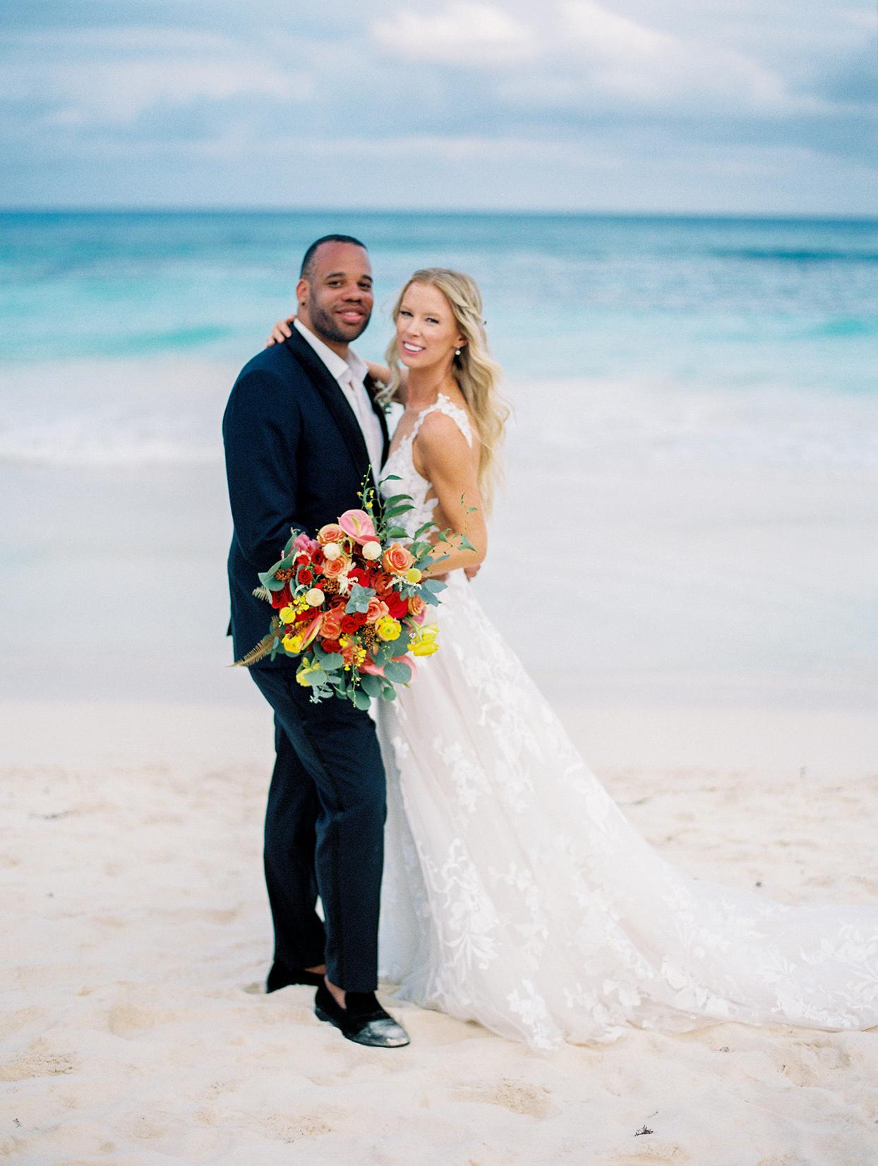 wedding couple posing for portrait on the beach