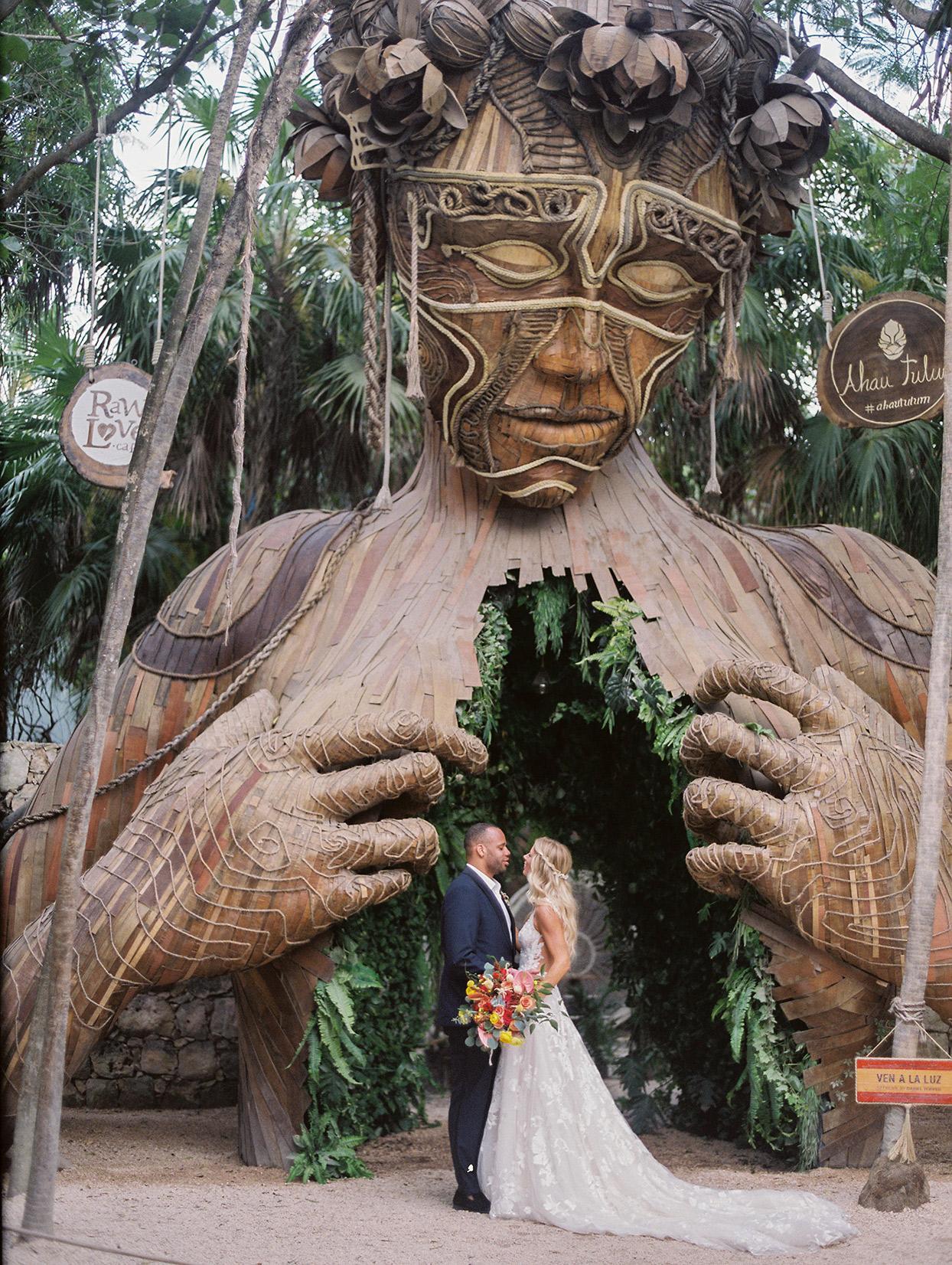 wedding couple posing under large artistic structure