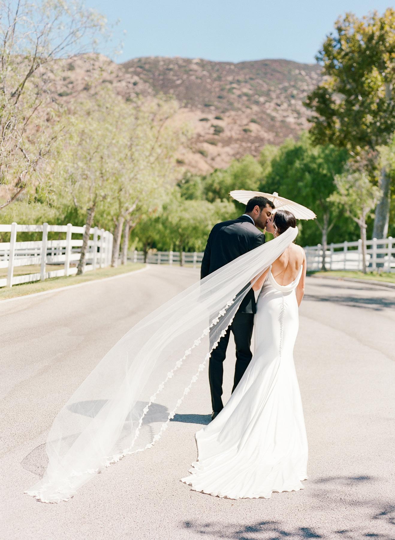 wedding couple kissing under parasol