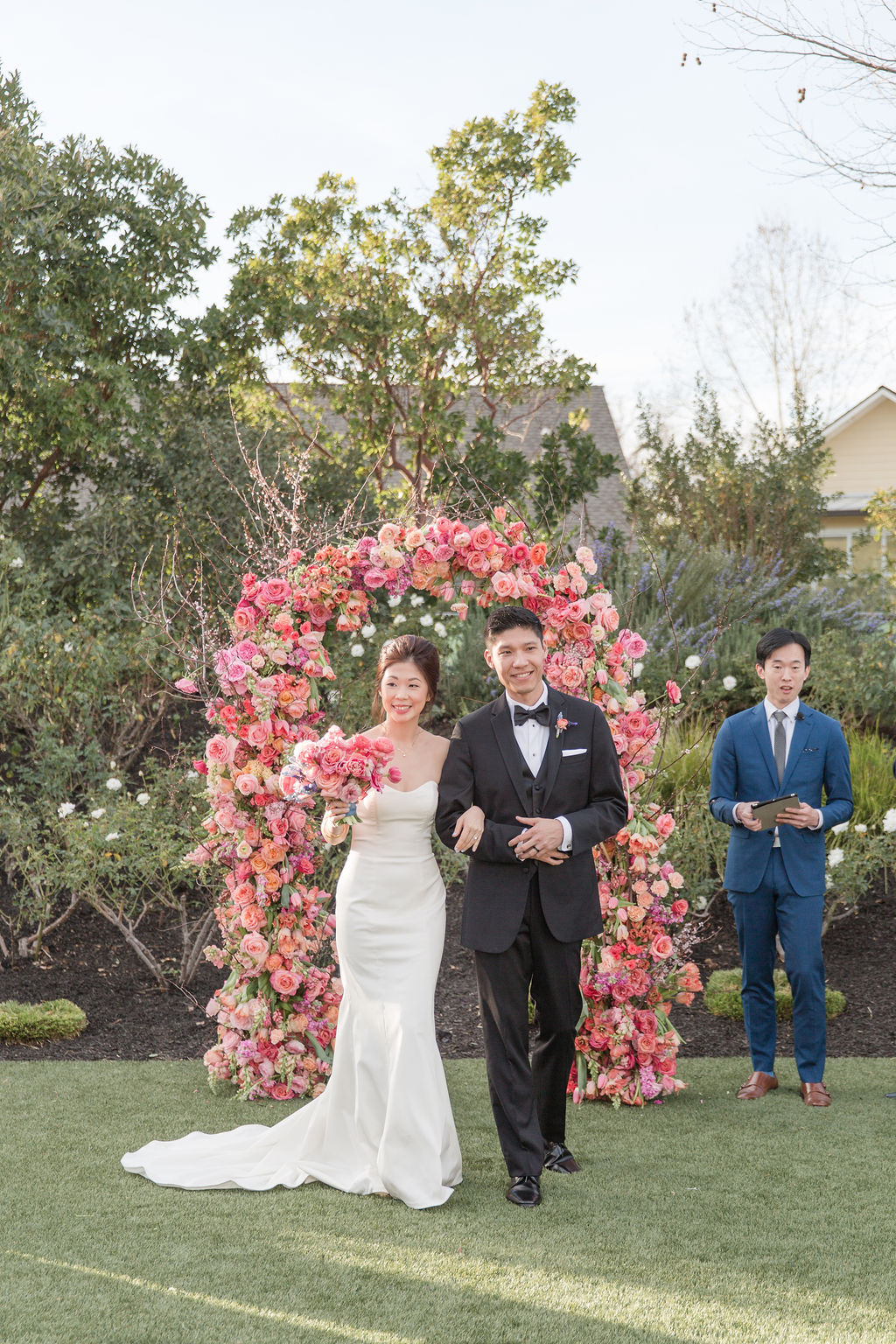 couple arm in arm at ceremony in front of floral pink arch
