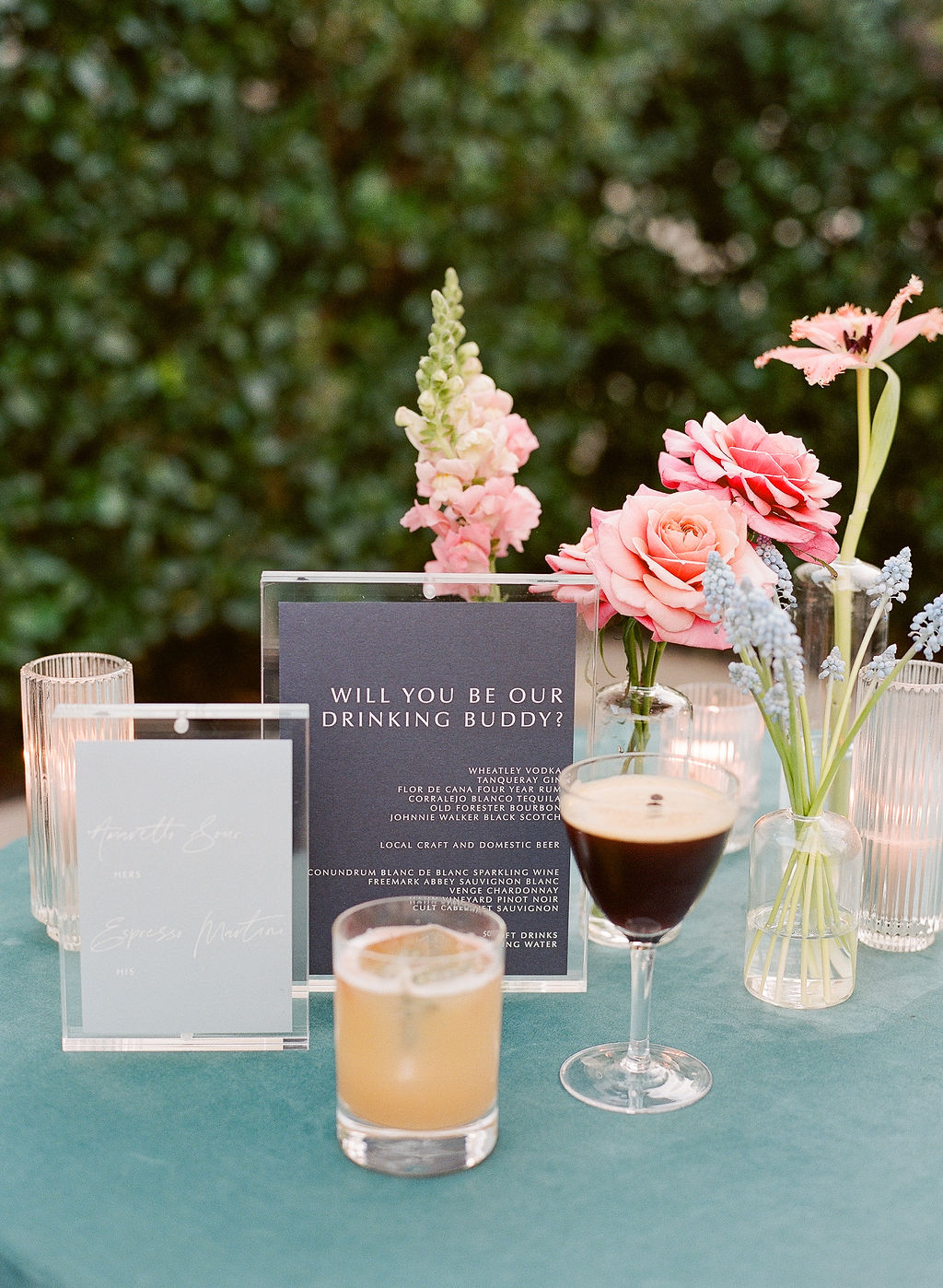 wedding cocktails on table with flowers and sign