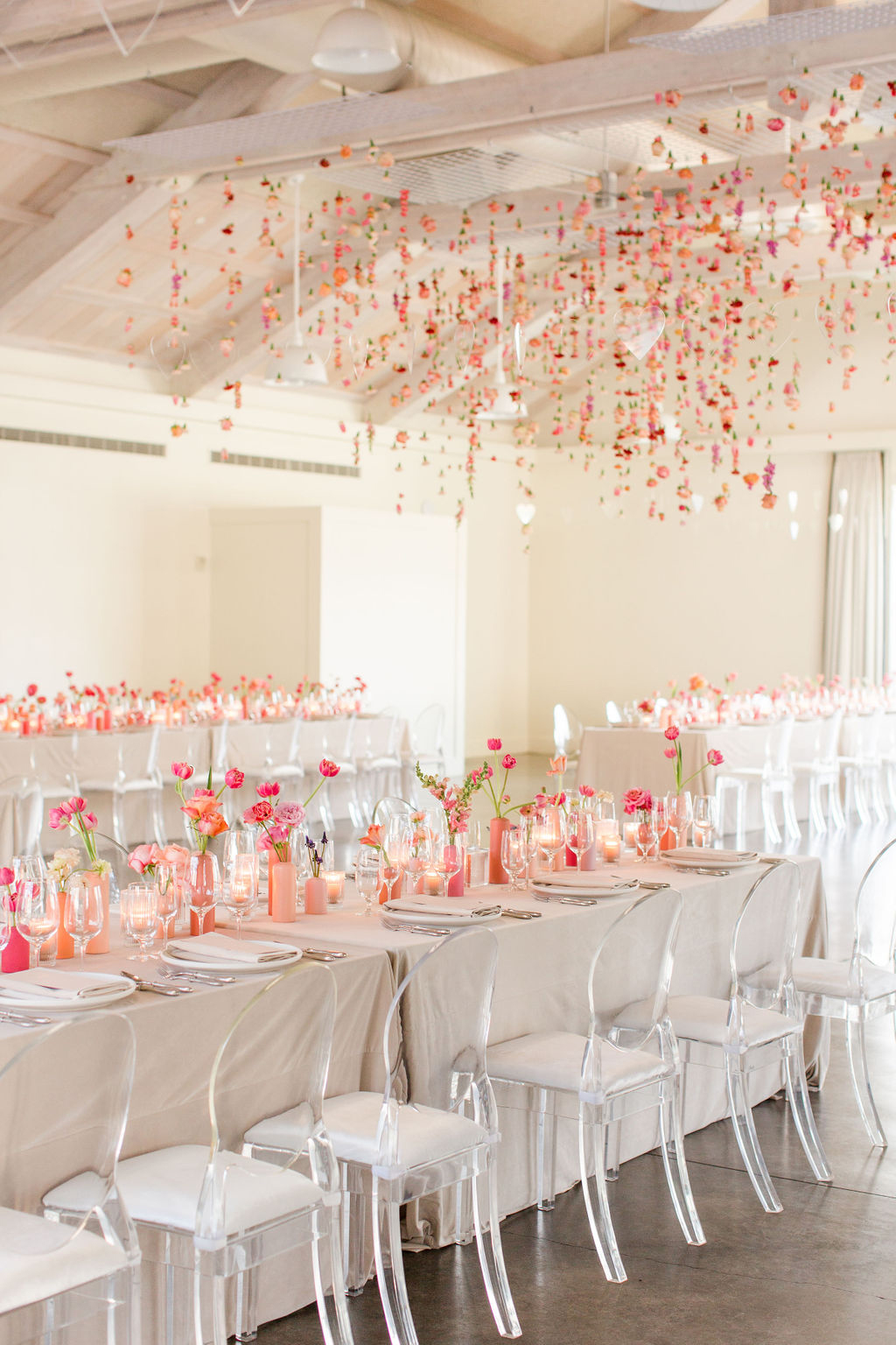 neutral and coral elegant wedding reception with clear chairs