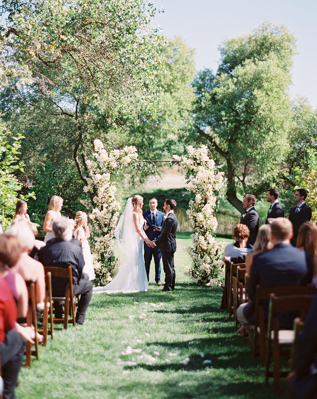 outdoor wedding ceremony vow exchange white floral arch