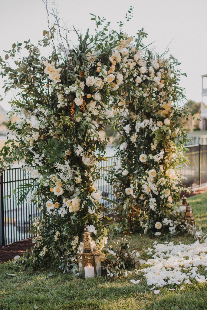 wedding arch comprised of various white flowers and greenery