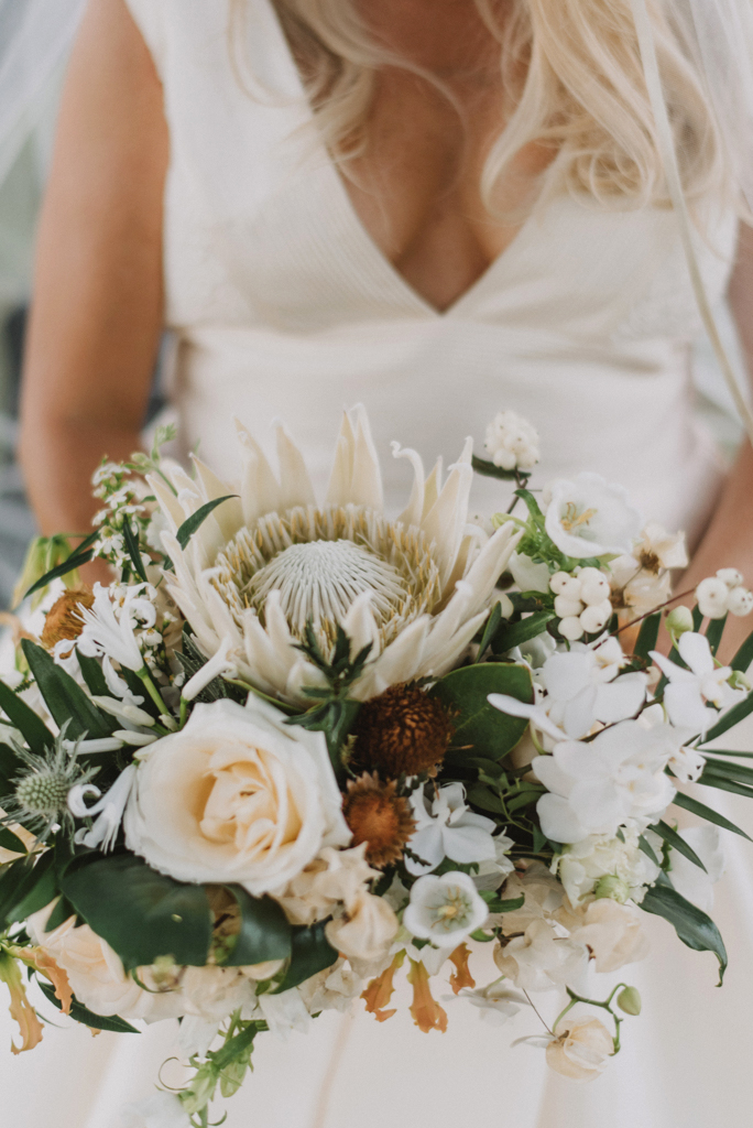 white bridal bouquet of proteas orchids and roses